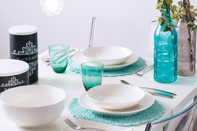 servizio piatti bianco con tovaglietta bottiglia e bicchieri azzurri