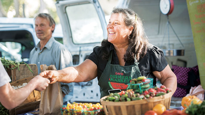 A woman vendor greets customers at the farmer's market