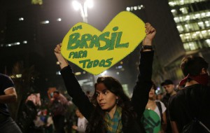 "A woman holds up a heart-shaped sign that reads in Portuguese ""One Brazil for all,"" on Paulista Avenue where crowds gathered to celebrate the reversal of a fare hike on public transportation, in Sao Paulo, Brazil, Thursday, June 20, 2013. After a week of mass protests, Brazilians won the world's attention and a pull-back on the subway and bus fare hikes that had first ignited their rage. Protesters gathered for a new wave of massive demonstrations in Brazil on Thursday evening, extending the protests that have sent hundreds of thousands of people into the streets since last week to denounce poor public services and government corruption. (AP Photo/Nelson Antoine)"