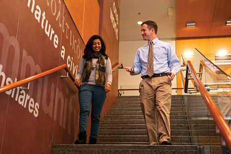 David and student walk down steps in Public Policy building