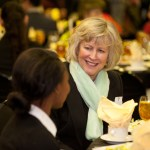 People sit at tables and talk at scholar luncheon