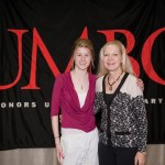 Women pose in front of UMBC flag at scholar luncheon