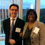 Two people with name tags pose at political science reception