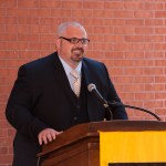 Man with glasses speaks from behind podium at Sherman Dedication