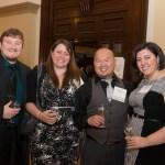Four professionally dressed people pose at wine tasting