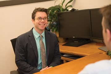 man in glasses and suit sits with monitors