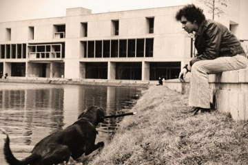 black and white photo of man at pond with dog