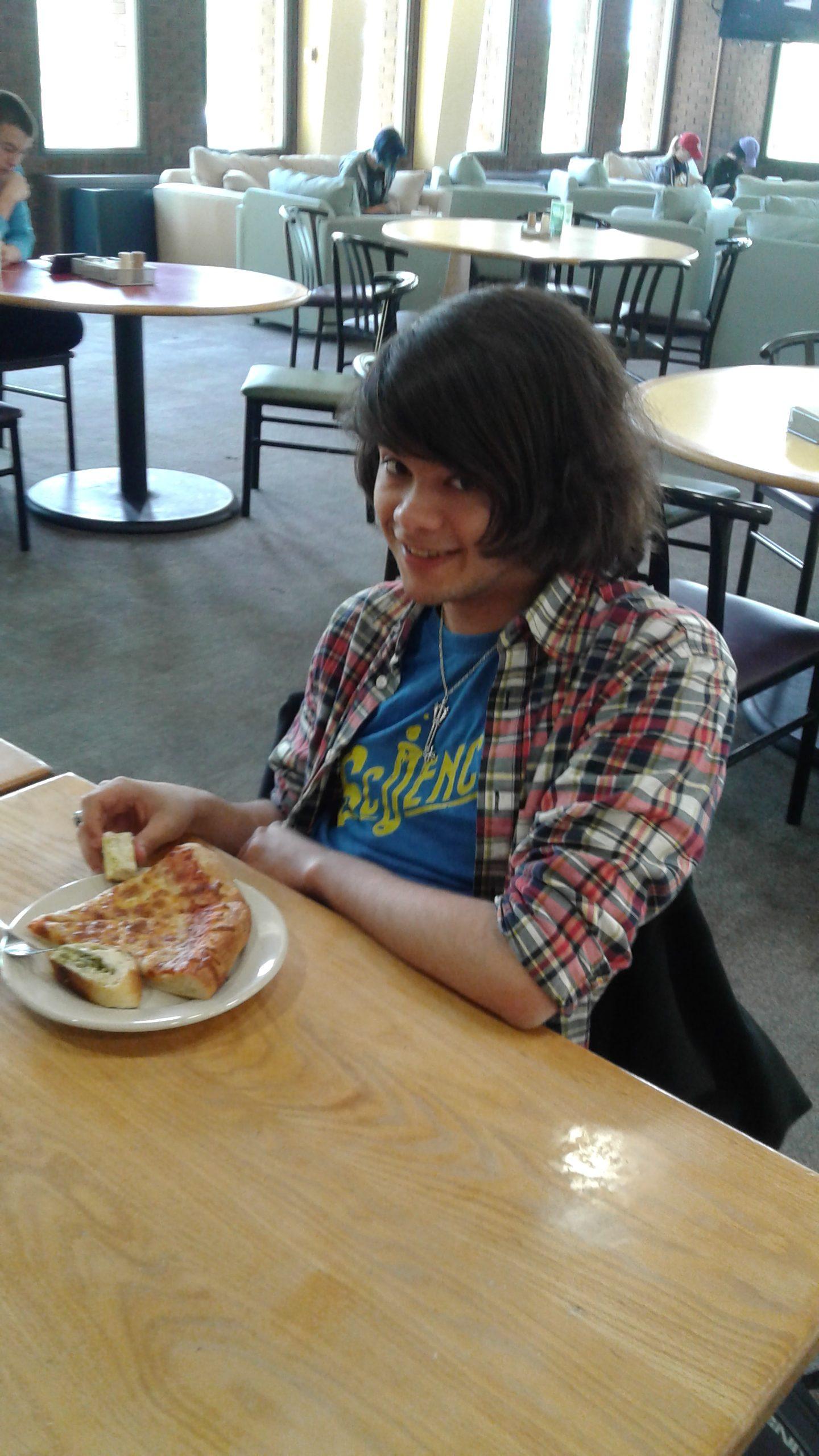 Anthony Deleon poses with pizza