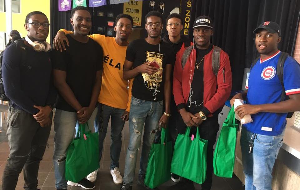 Group of male students posing with green care packages