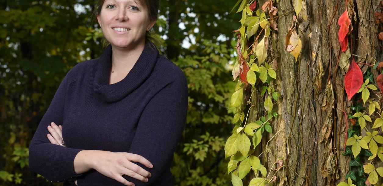 Woman poses next to a tree