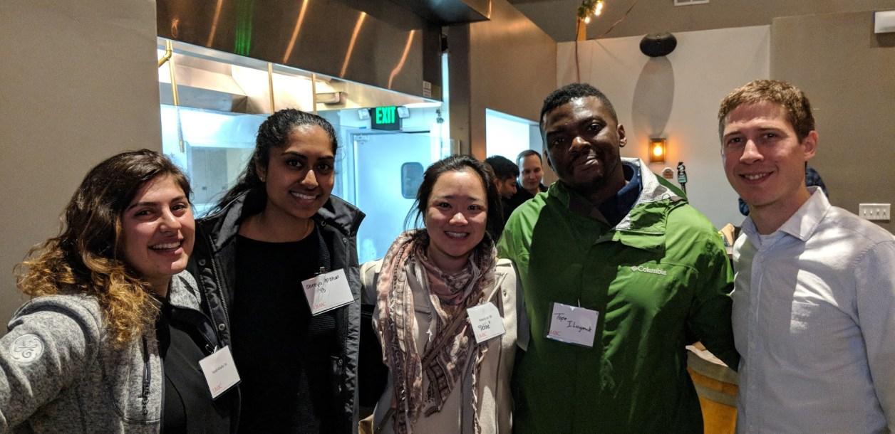 Bay area alumni pose together with name tags
