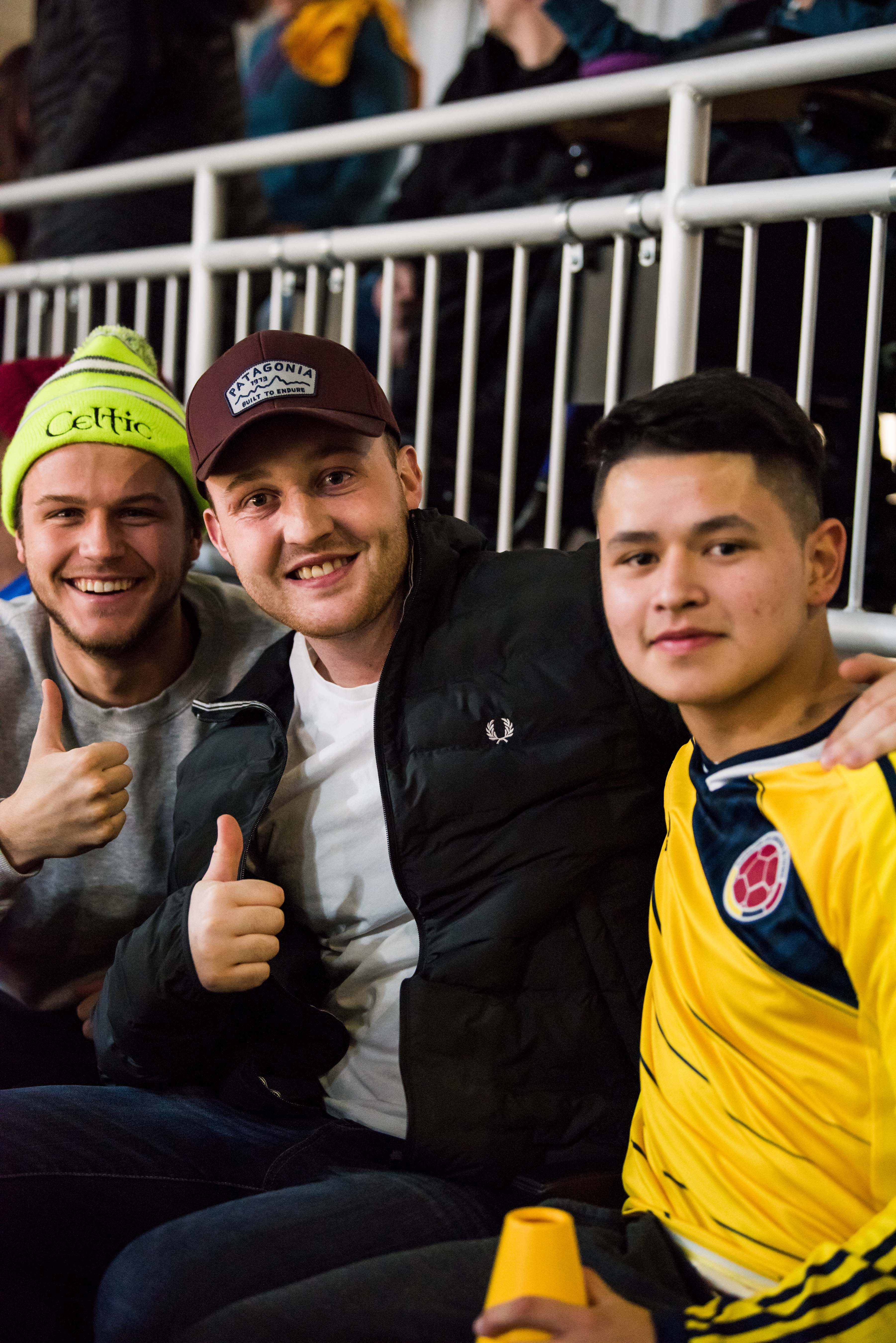 Three people in stands pose together holding up thumbs up signs