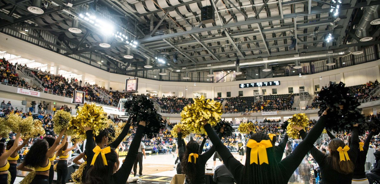 Cheerleaders wave their pom poms at event center opening