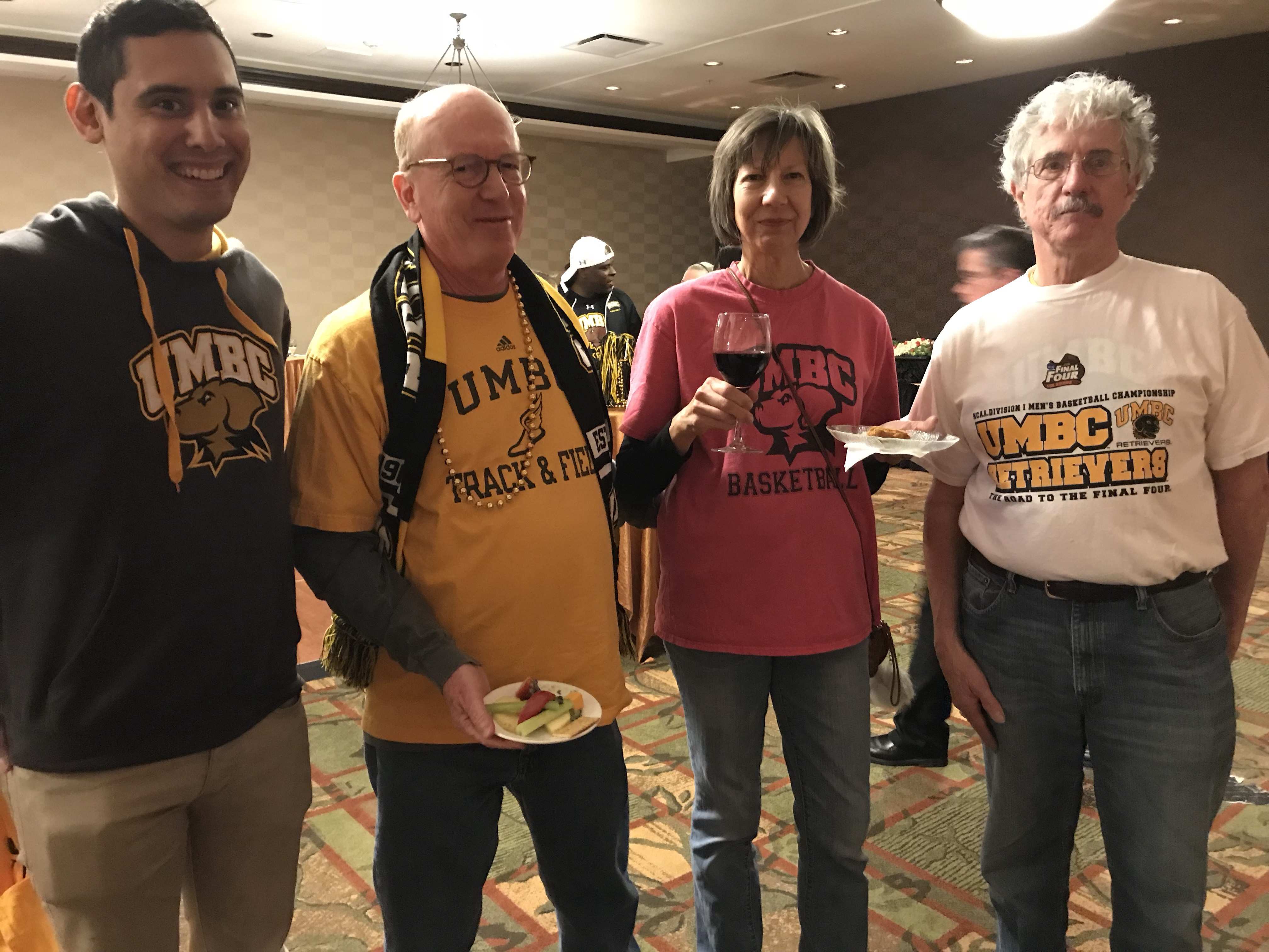 Four people with UMBC shirts on pose for picture