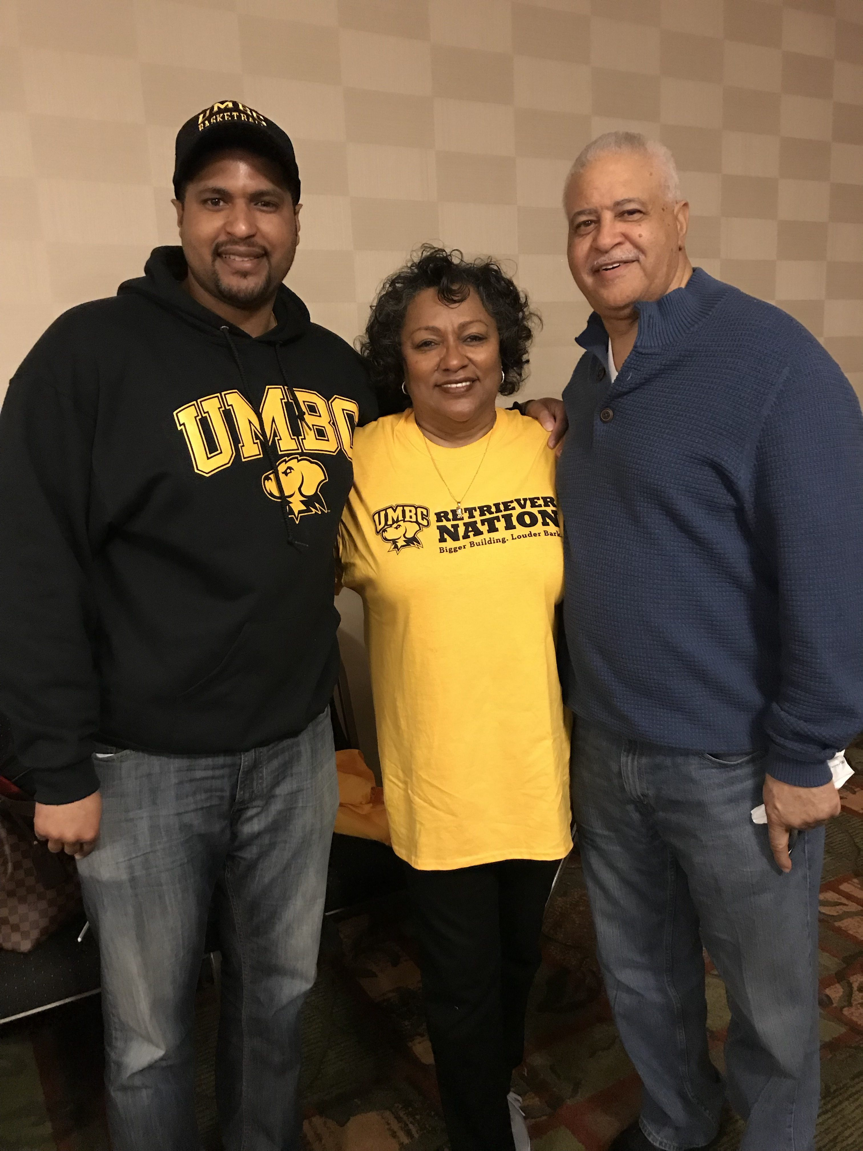 Three fans in UMBC gear pose together