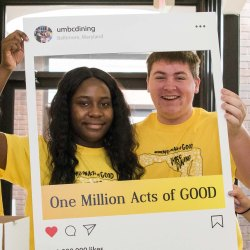 Two people hold one million acts of good frame while two people pose inside frame