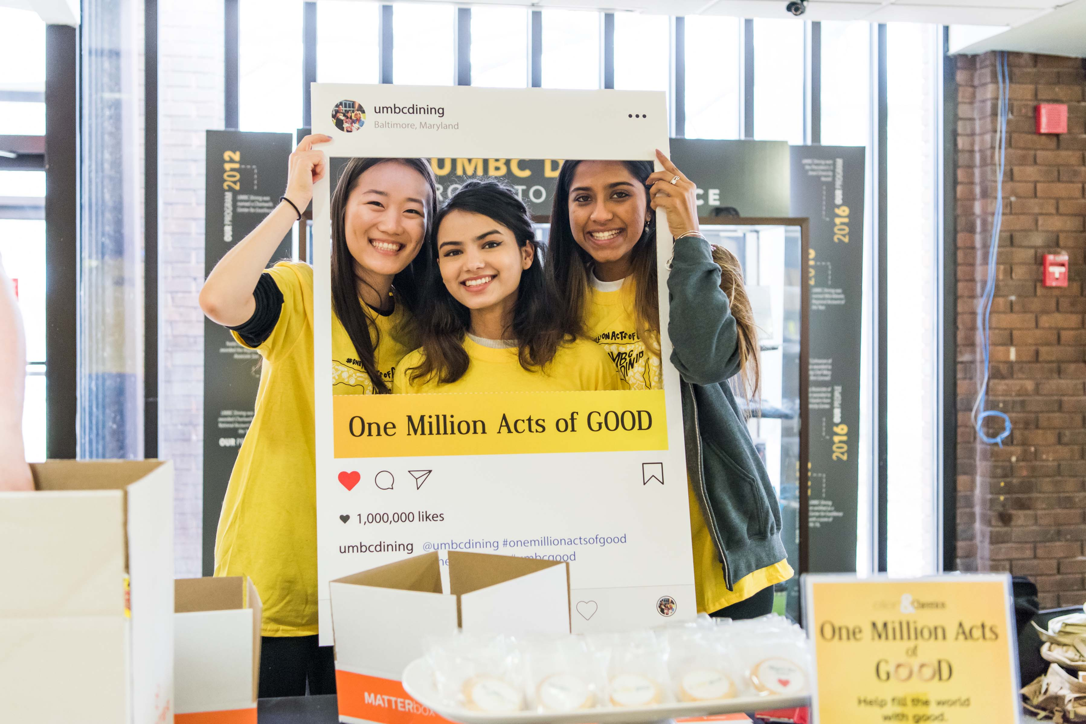 Three girls pose with One million acts of good frame