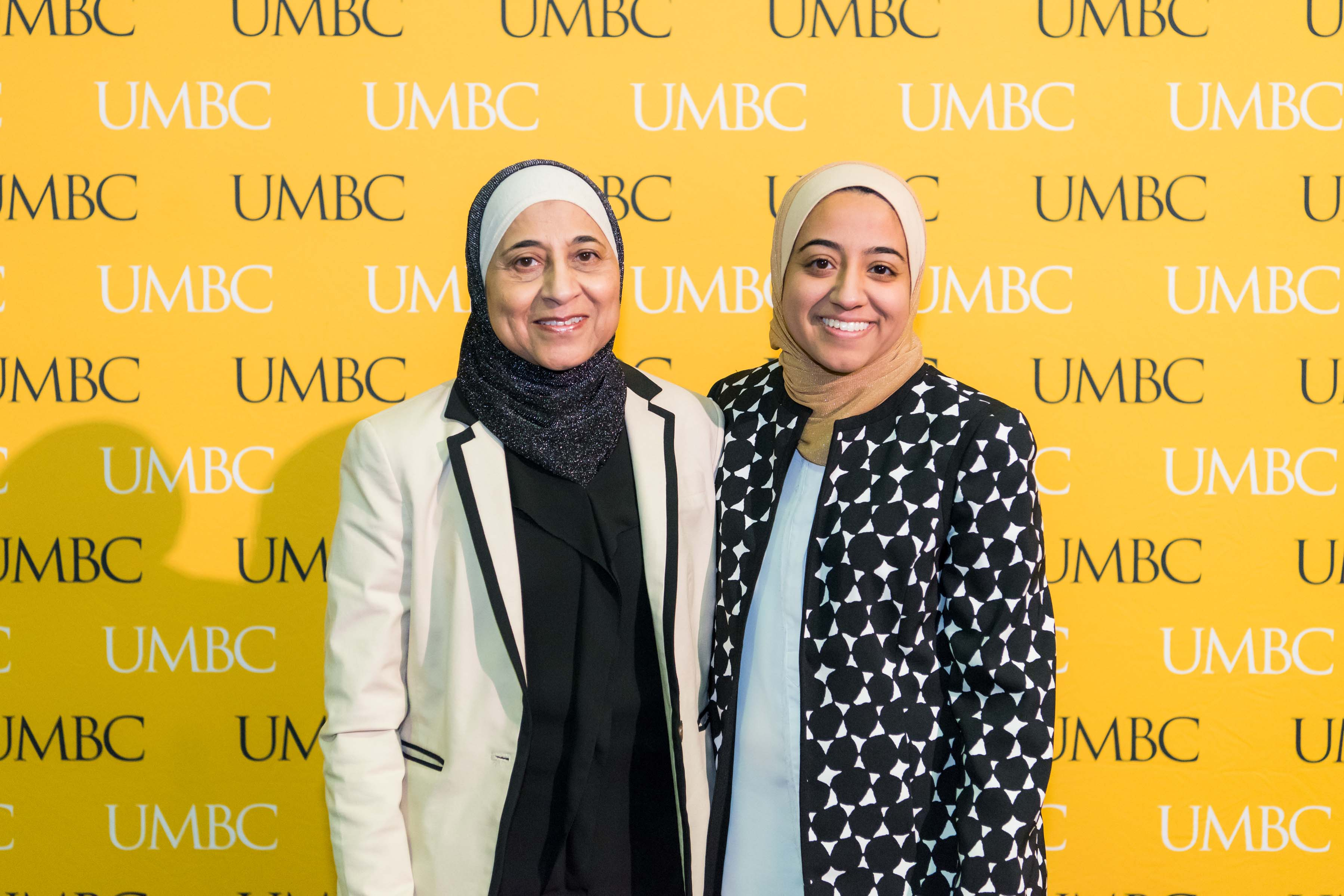 Two women in hijab pose in front of the UMBC wall at the scholarship luncheon