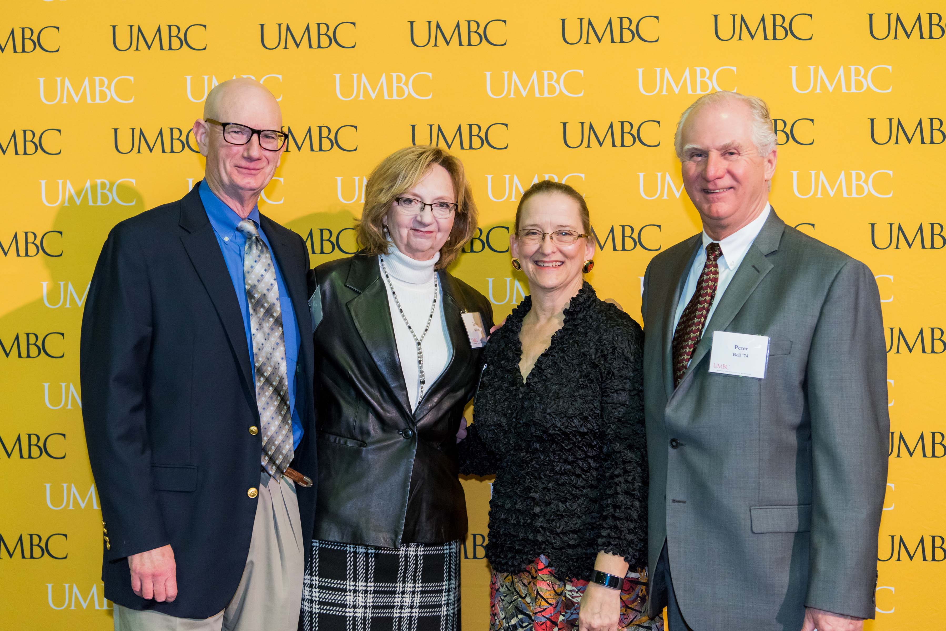 Group of four pose in front of the UMBC wall at the scholarship luncheon