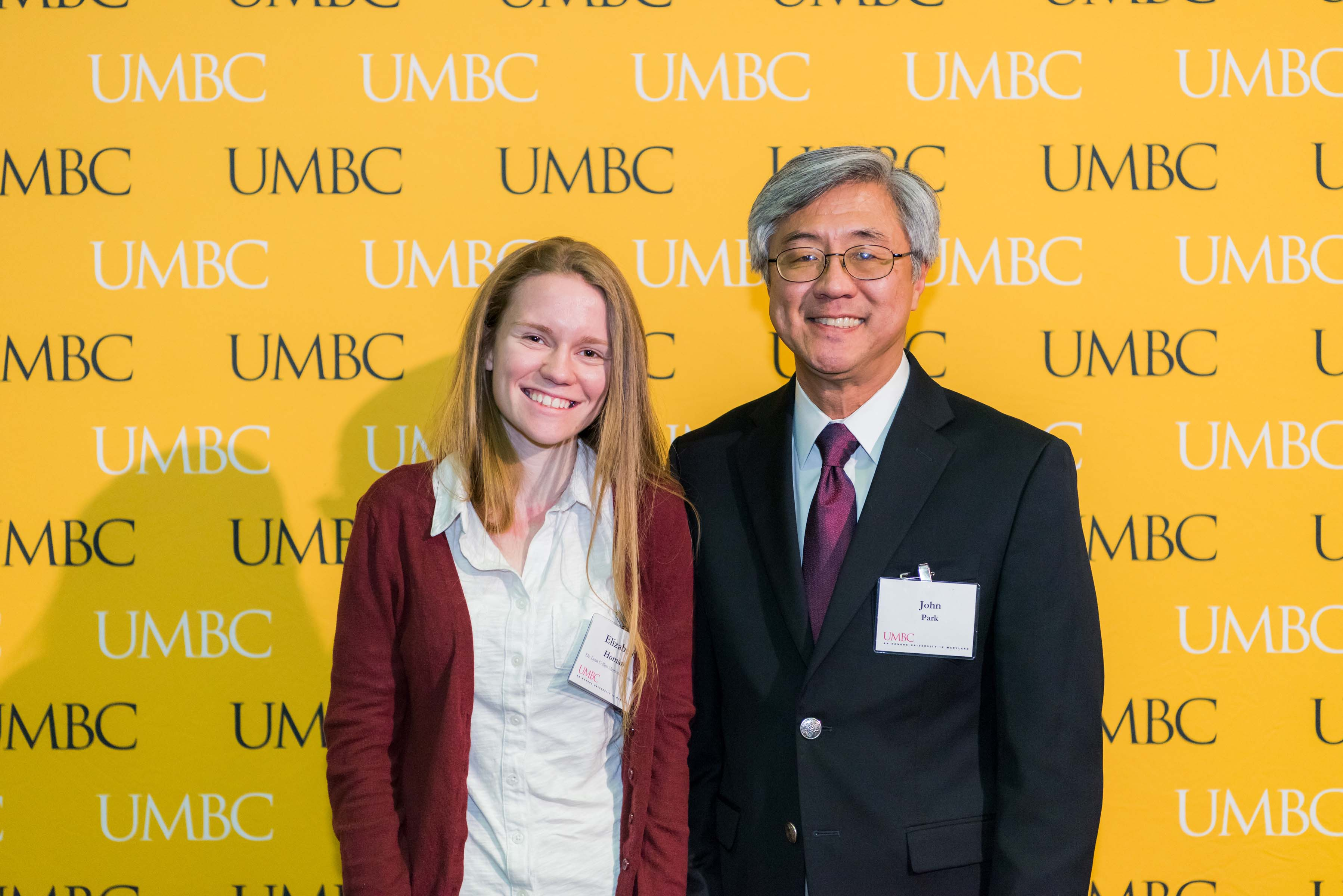 Two people pose in front of the UMBC wall at the scholarship luncheon