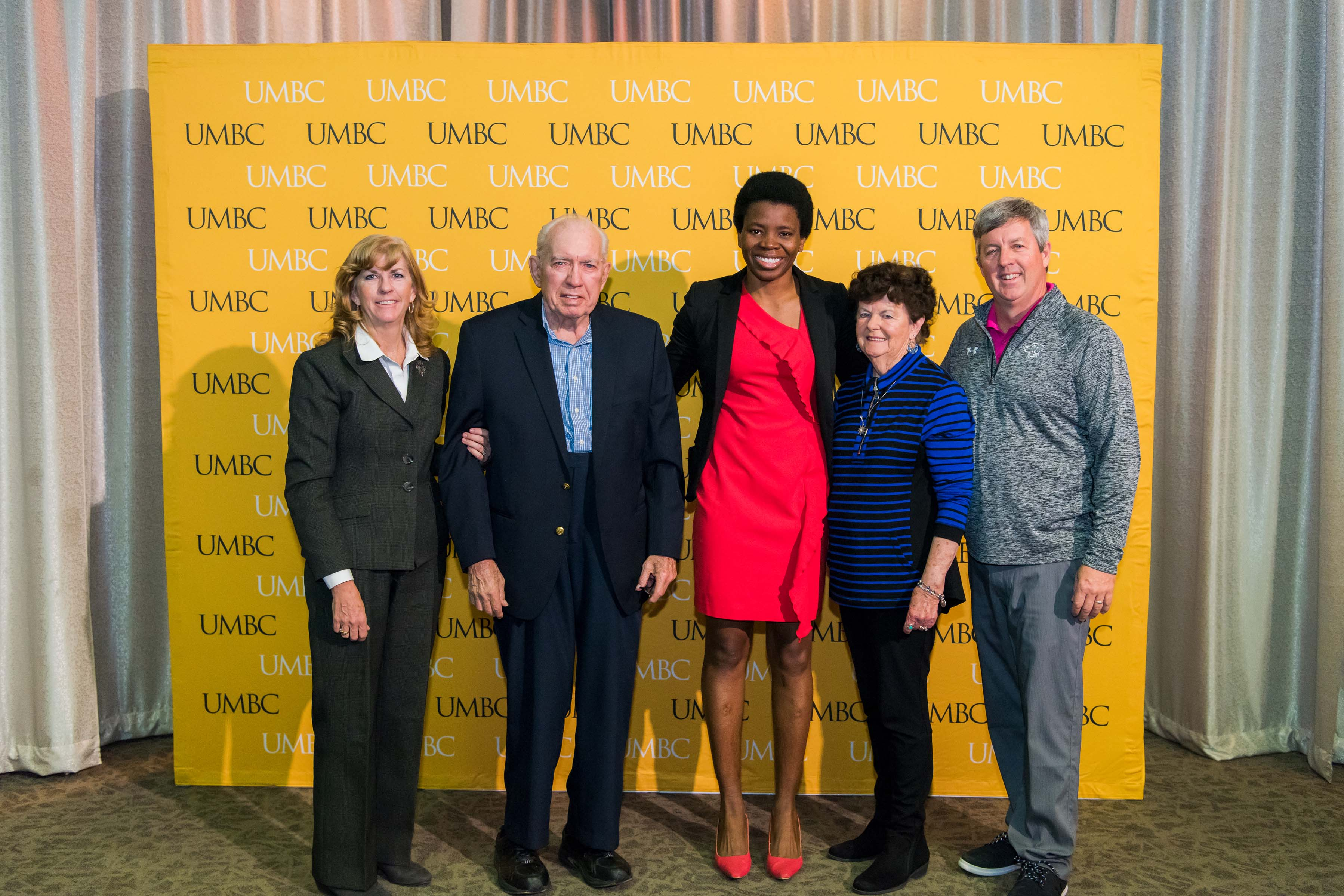 Group of five pose in front of the UMBC wall at the scholarship luncheon