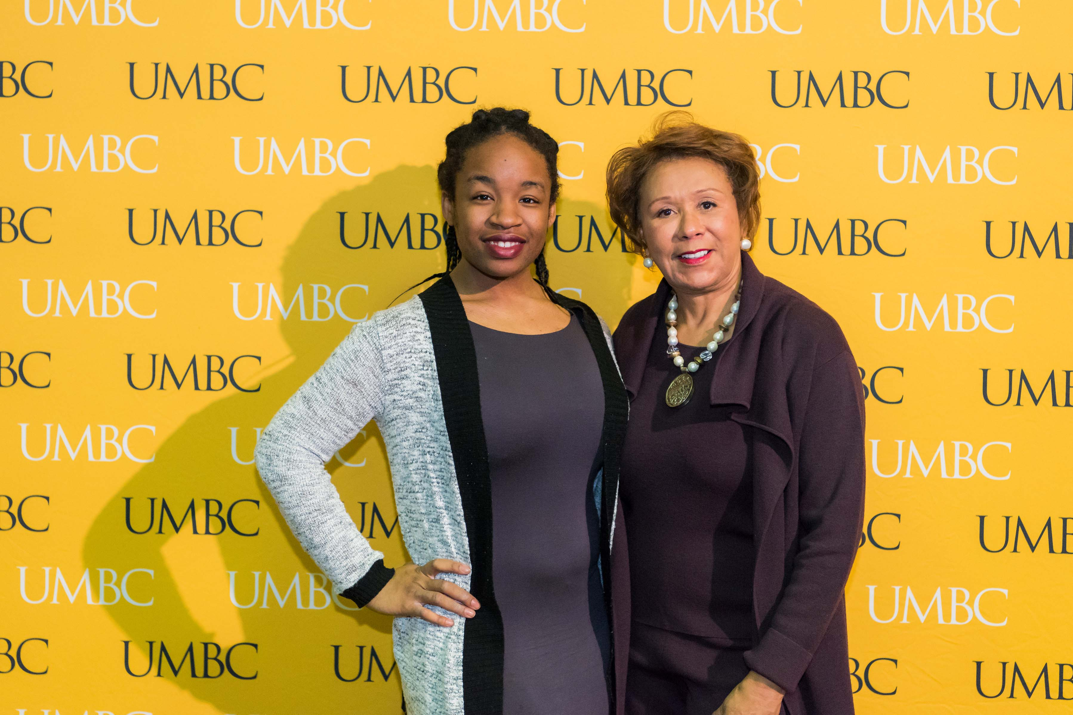 Women and Jacqueline Hrabowski pose in front of the UMBC wall at the scholarship luncheon