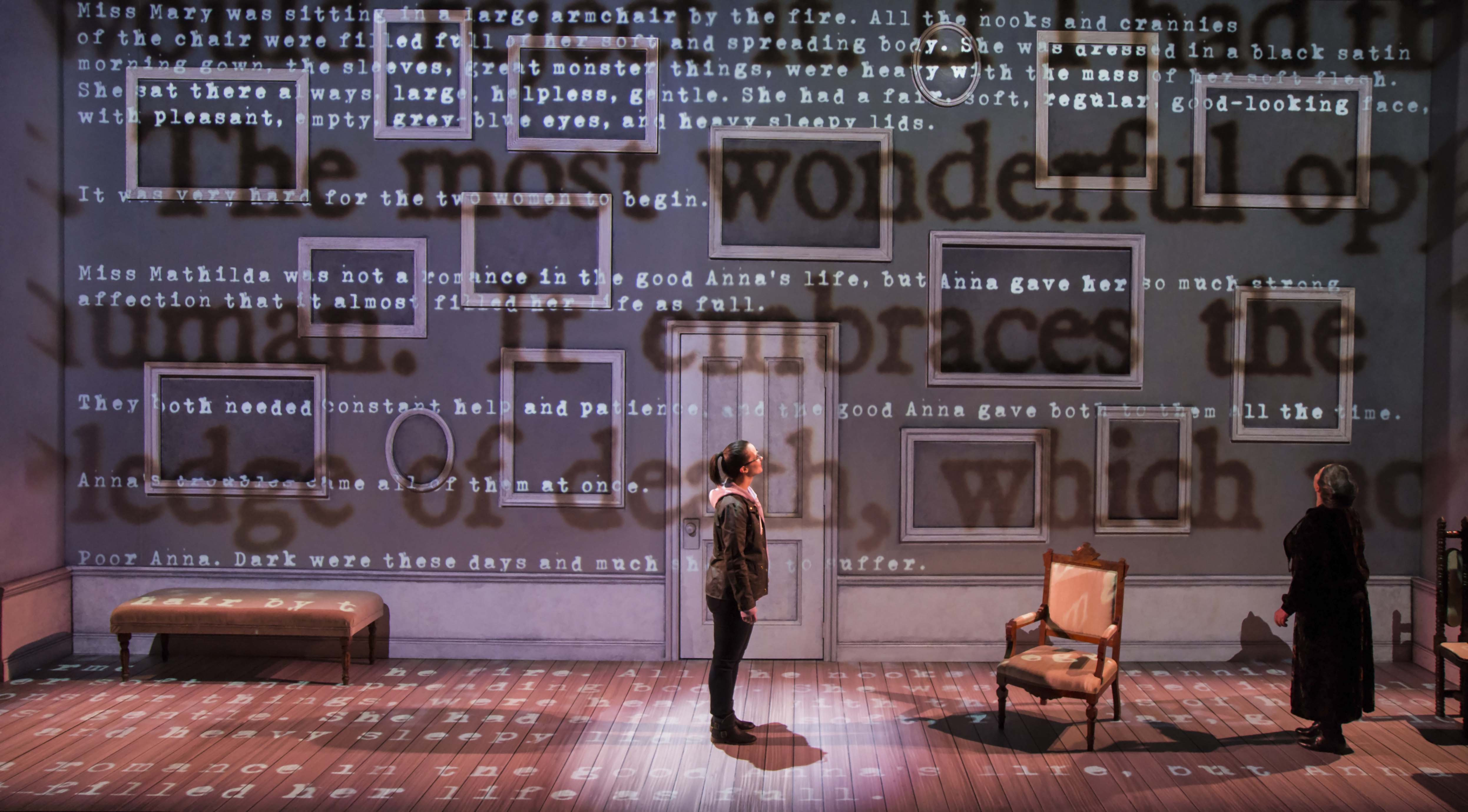 Woman stand center stage words projected on wall and floor