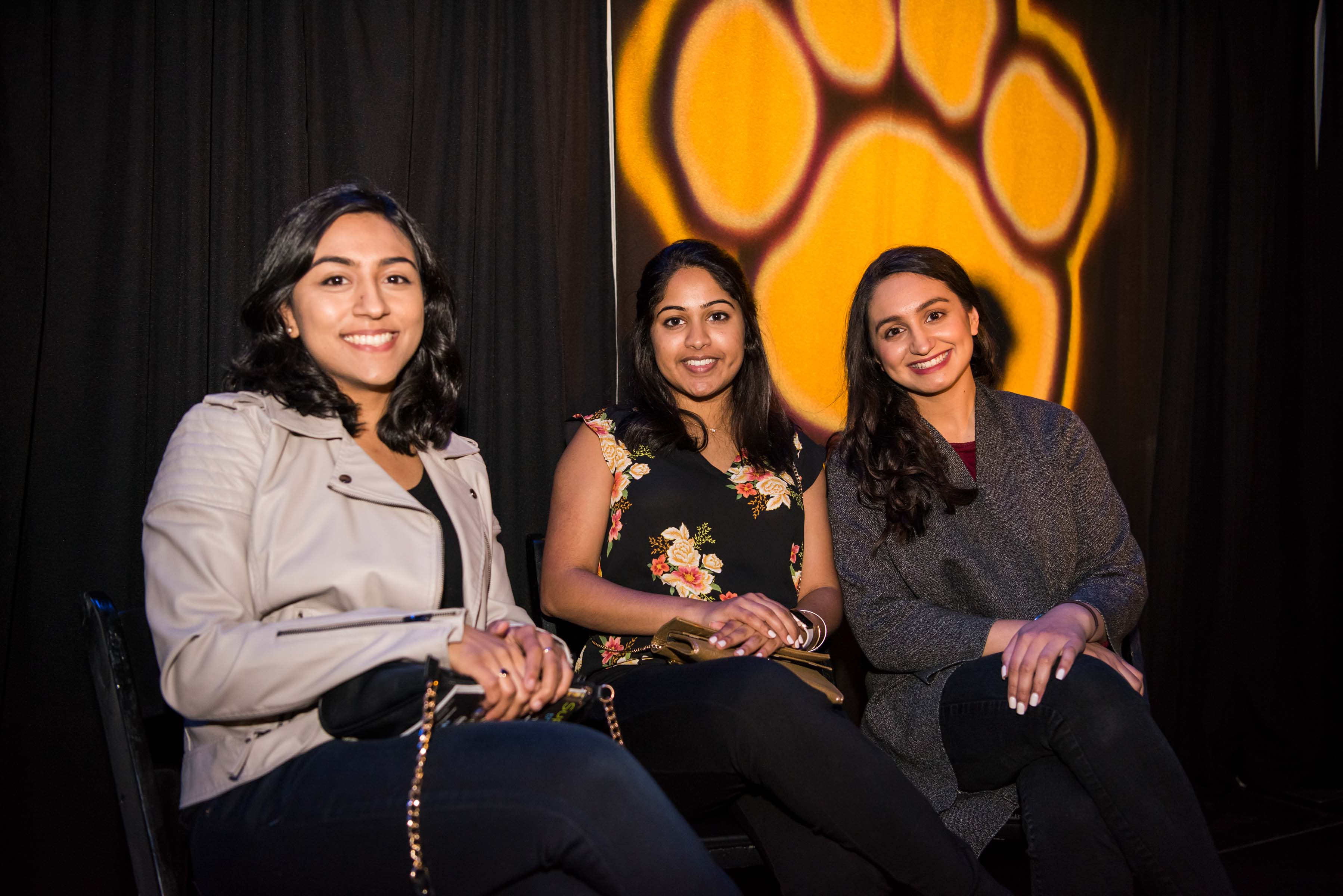 Three women sit umbc paw illuminated on curtains behind them