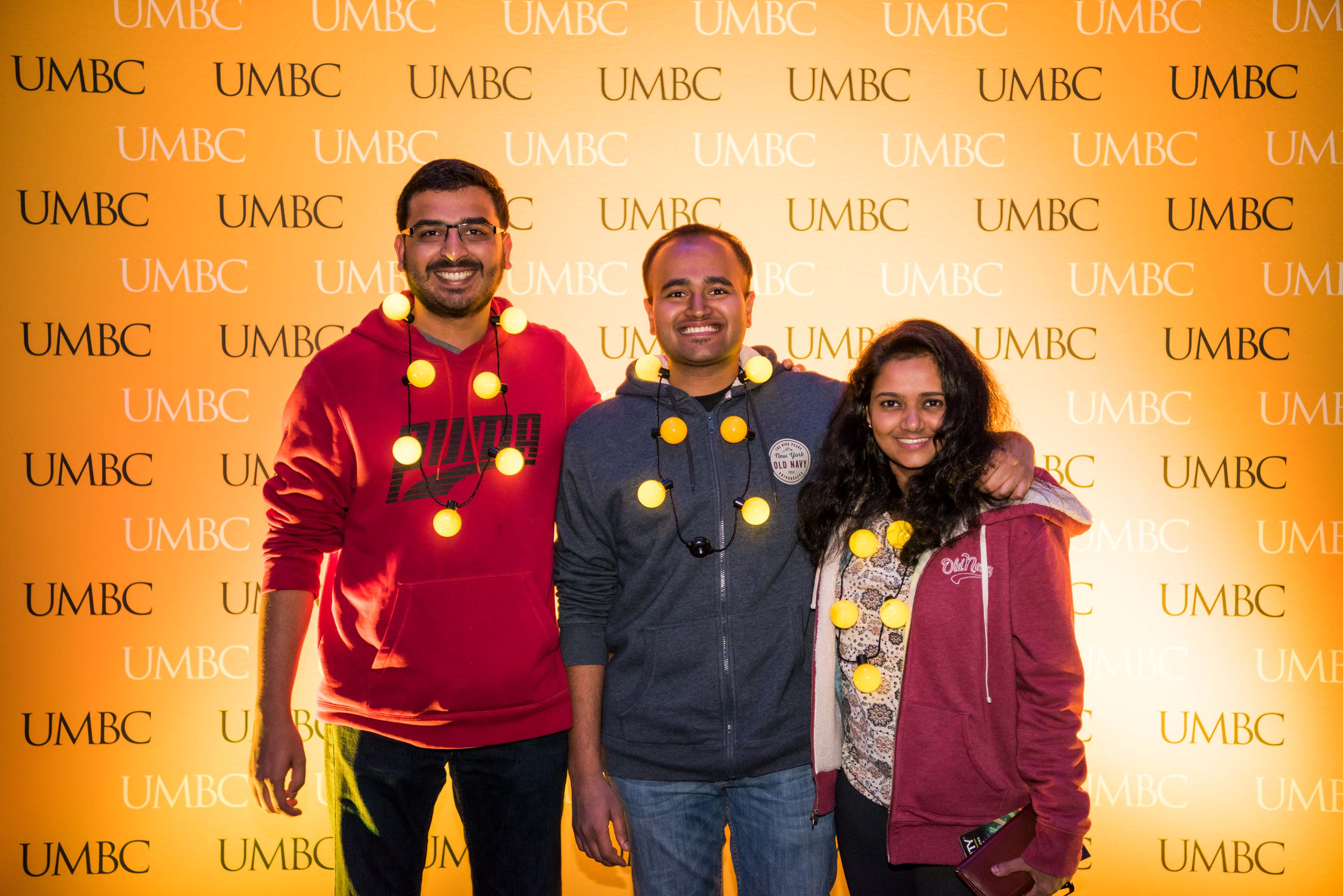Three people pose in front of UMBC wall at alumni reception