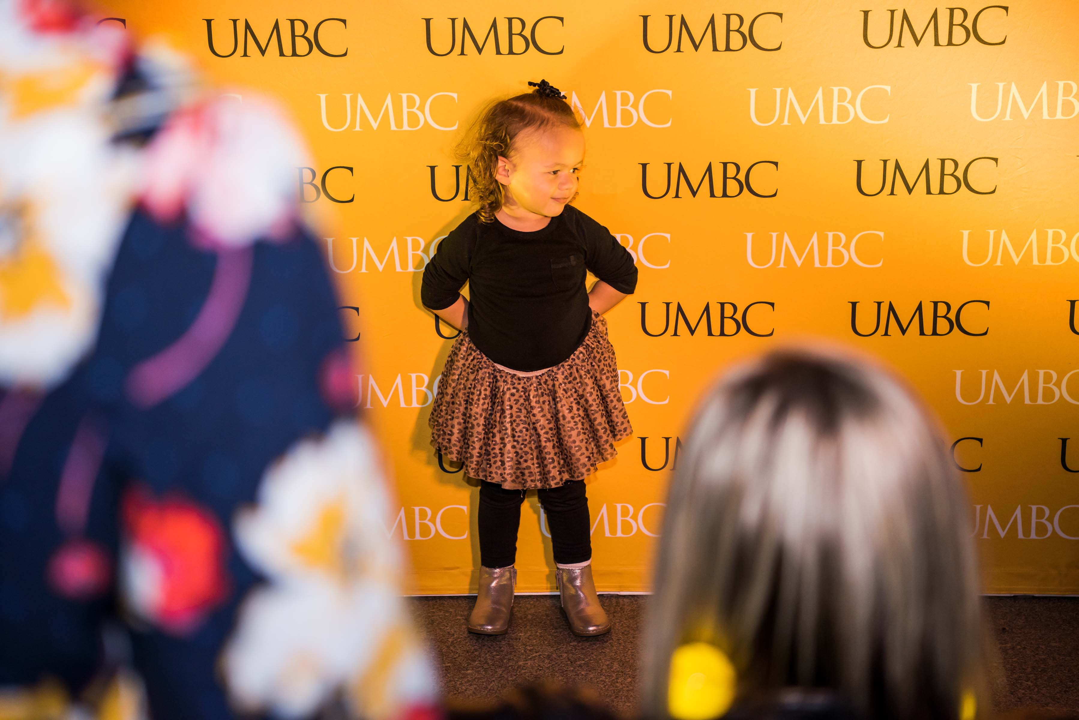 little girl pose in front of UMBC wall at alumni reception