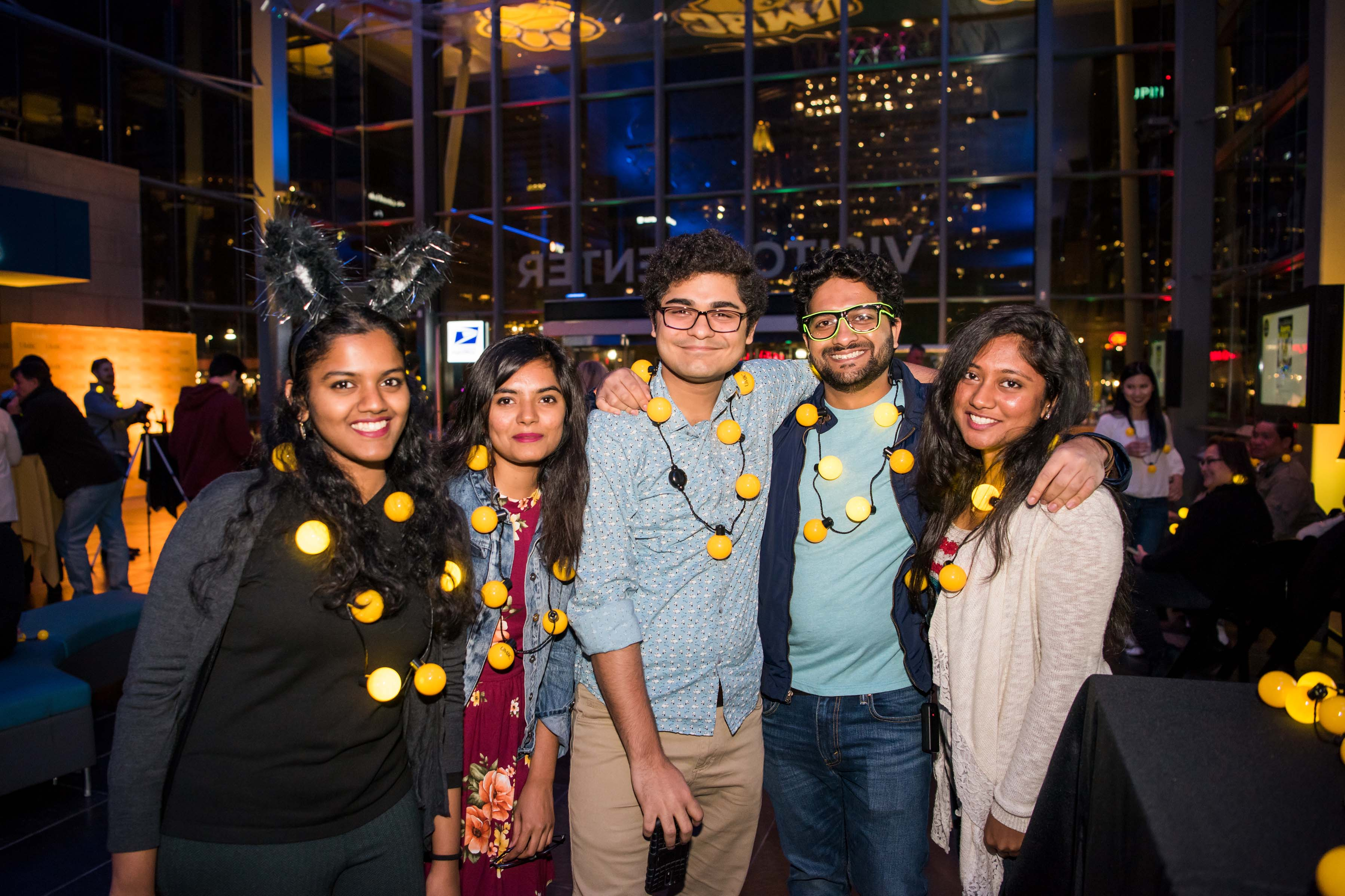 Group of five friends pose in lobby with light bulb necklaces at alumni reception