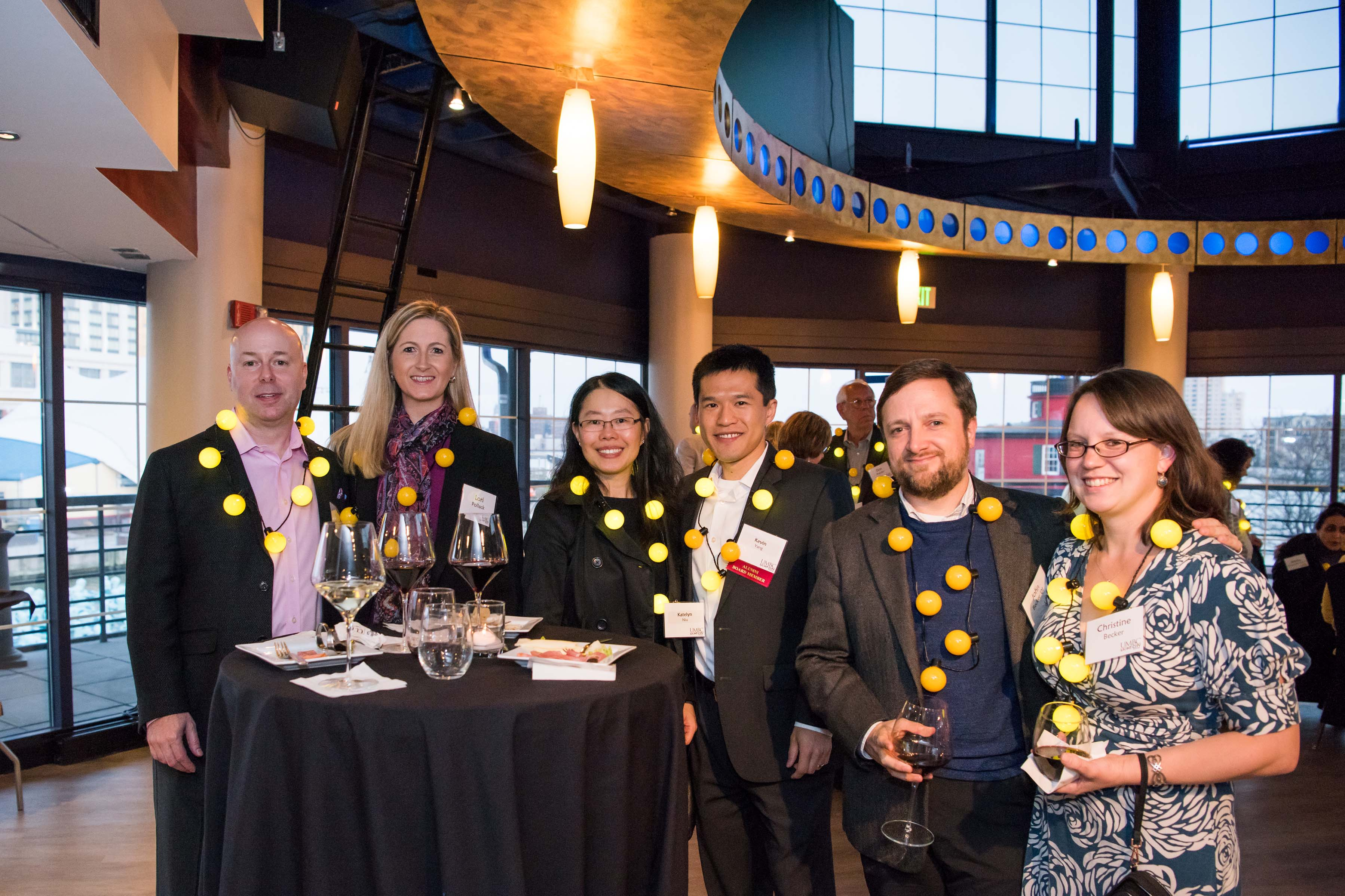 Group of six pose around round table at Pier5 reception