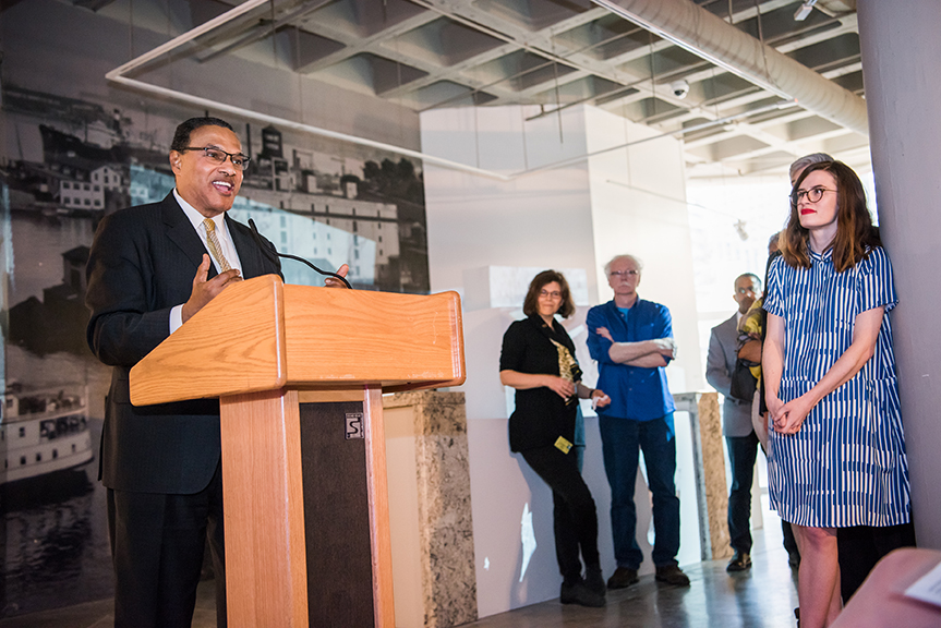 Hrabowski stands behind podium and gives speech people watching at light city alumni reception