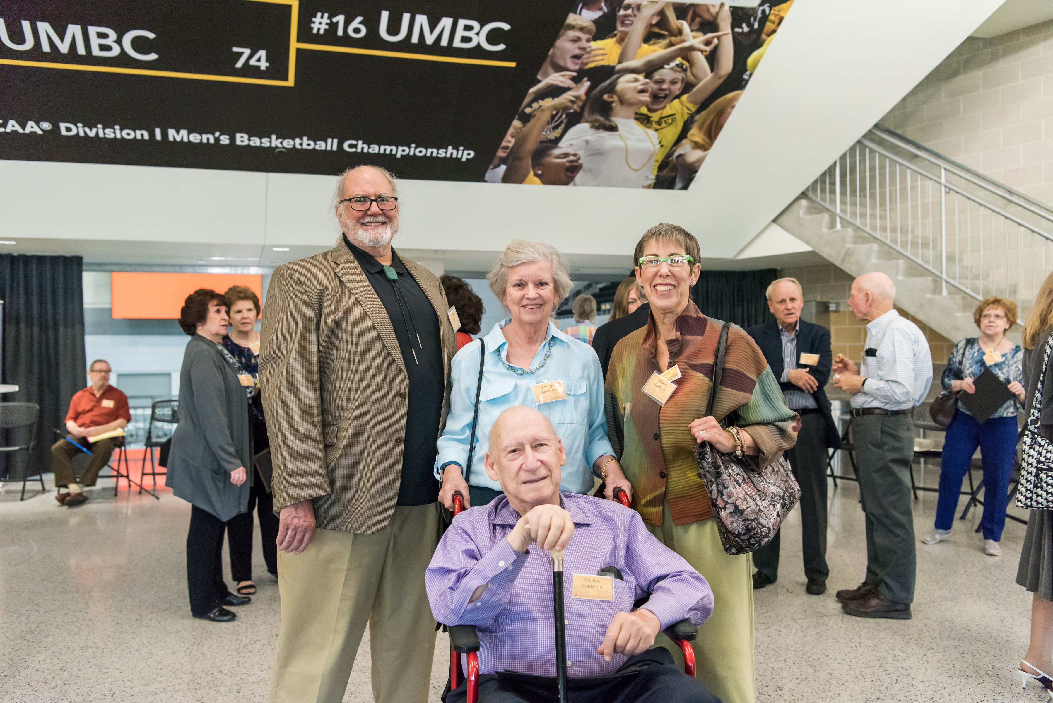Group of four pose together UMBC sign behind them at Wisdom Institute lunch