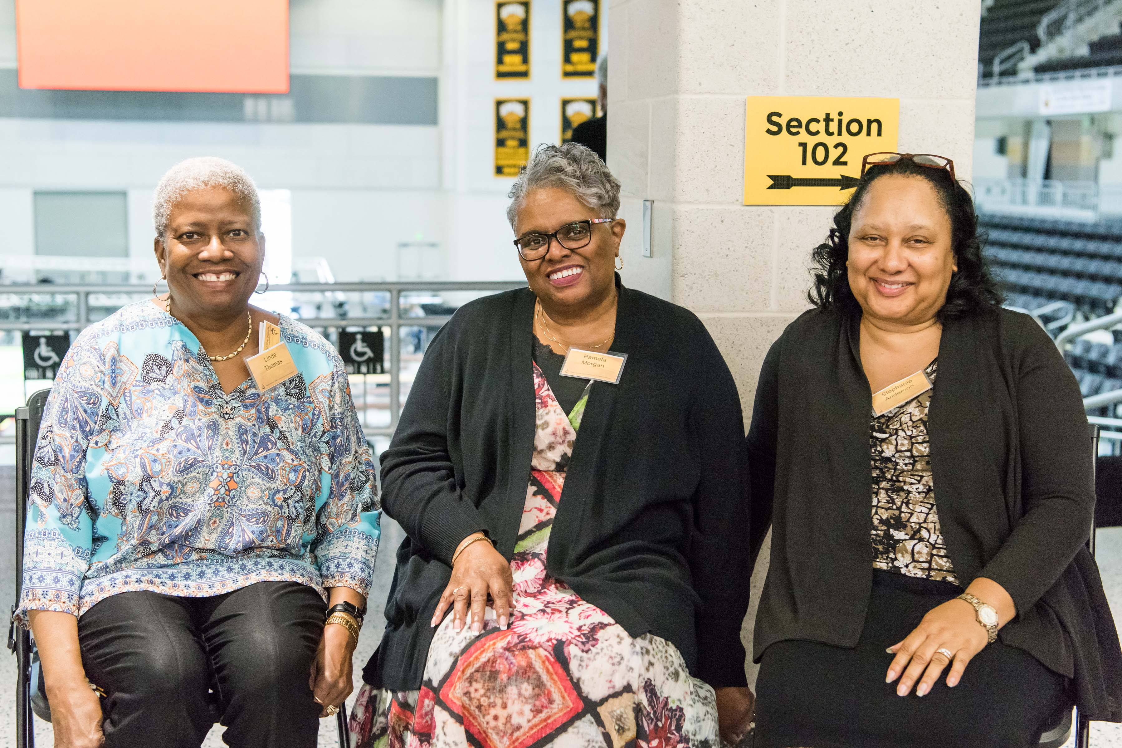 Three women sit and pose at Wisdom Institute lunch