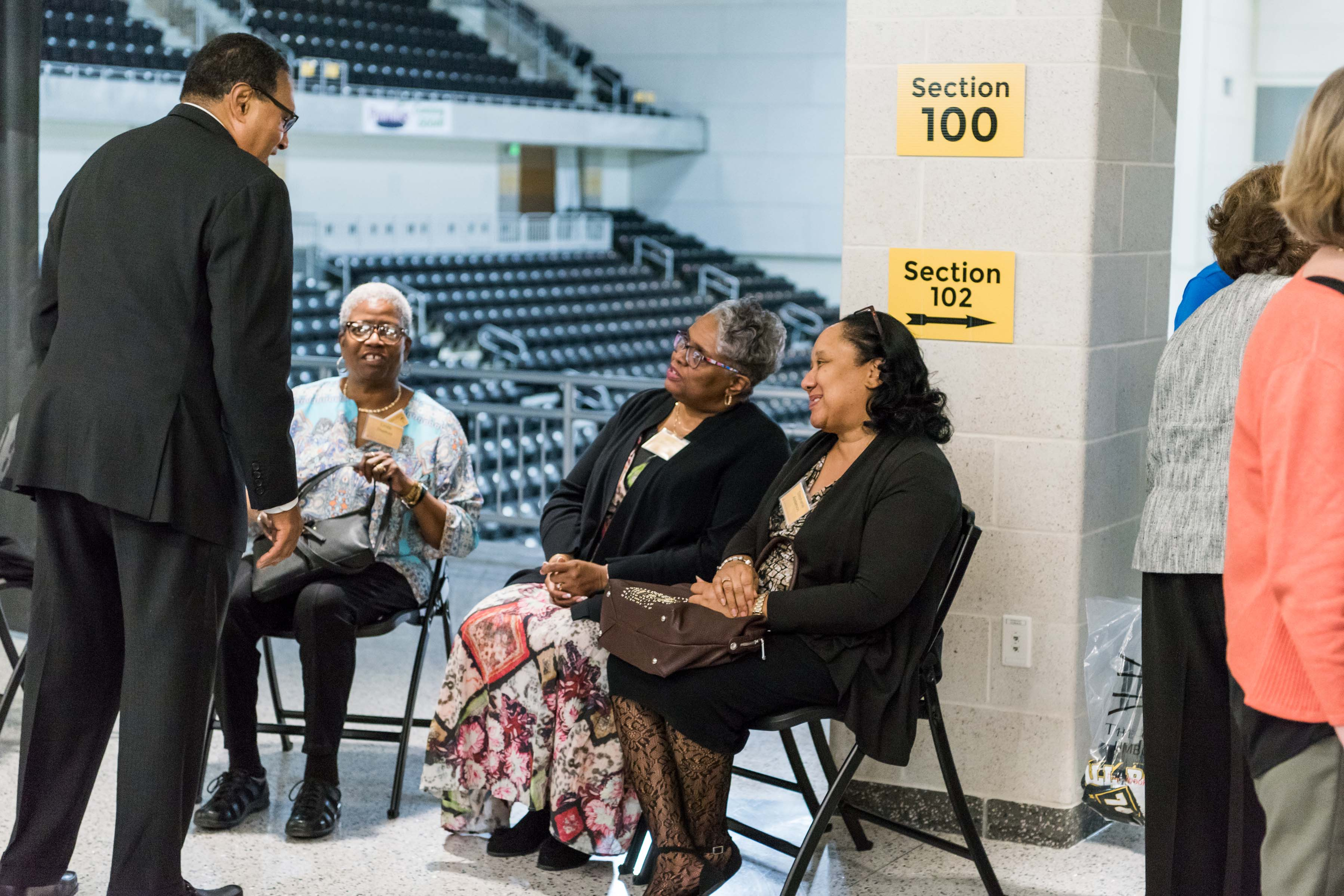 Hrabowski approaches women sitting at Wisdom Institute lunch