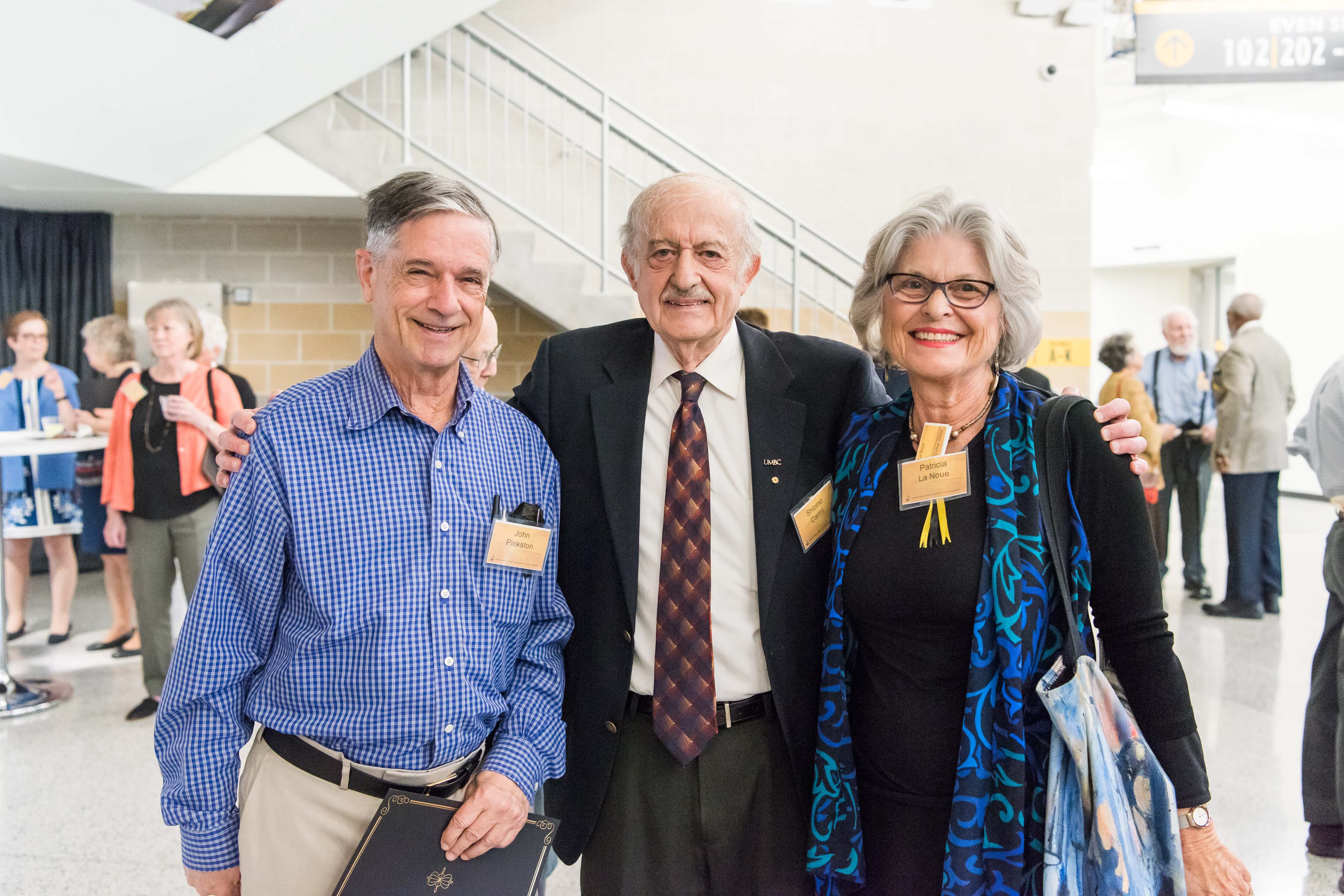 Three people pose together at Wisdom Institute lunch