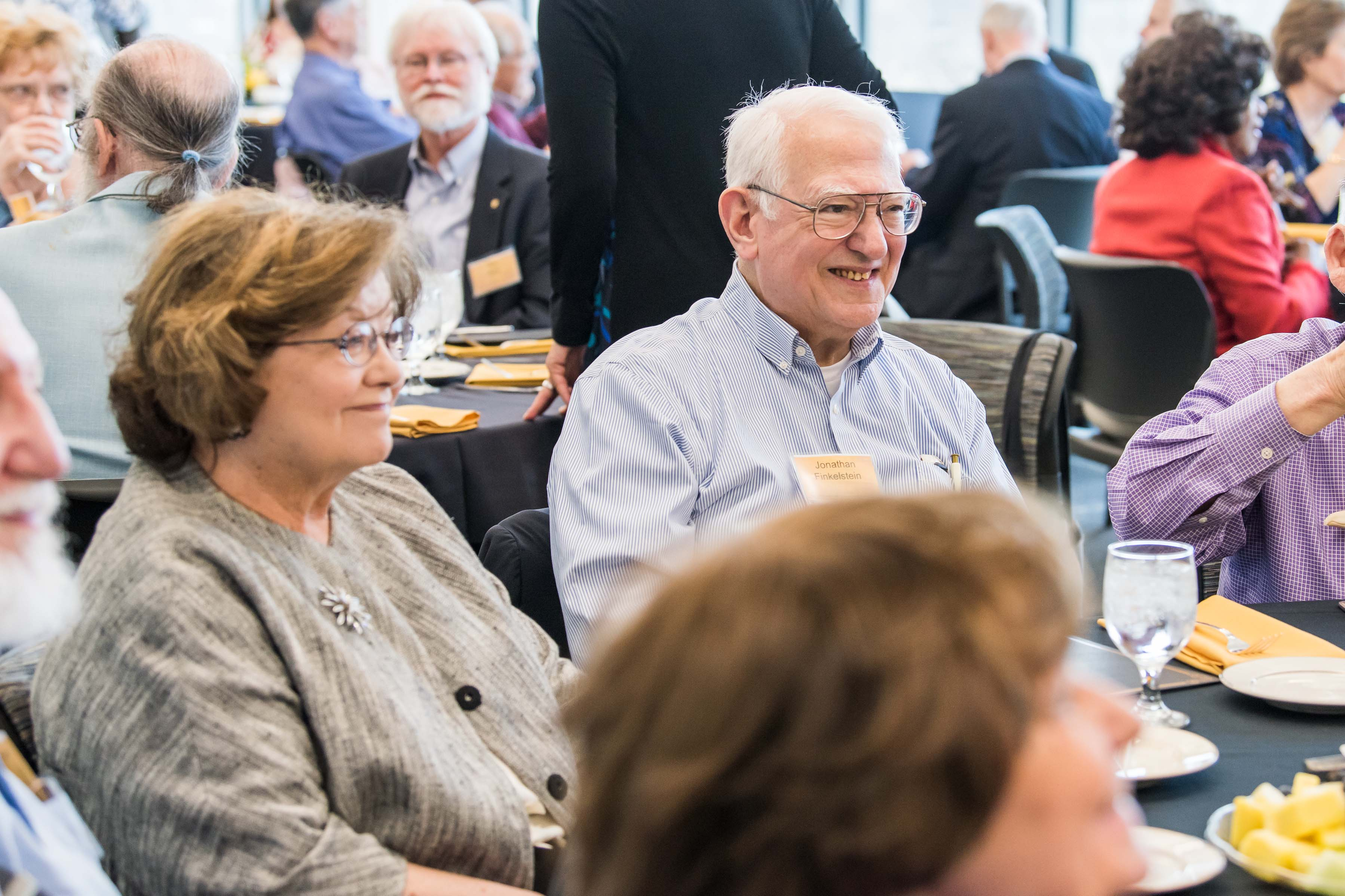 People smile at table at Wisdom Institute lunch