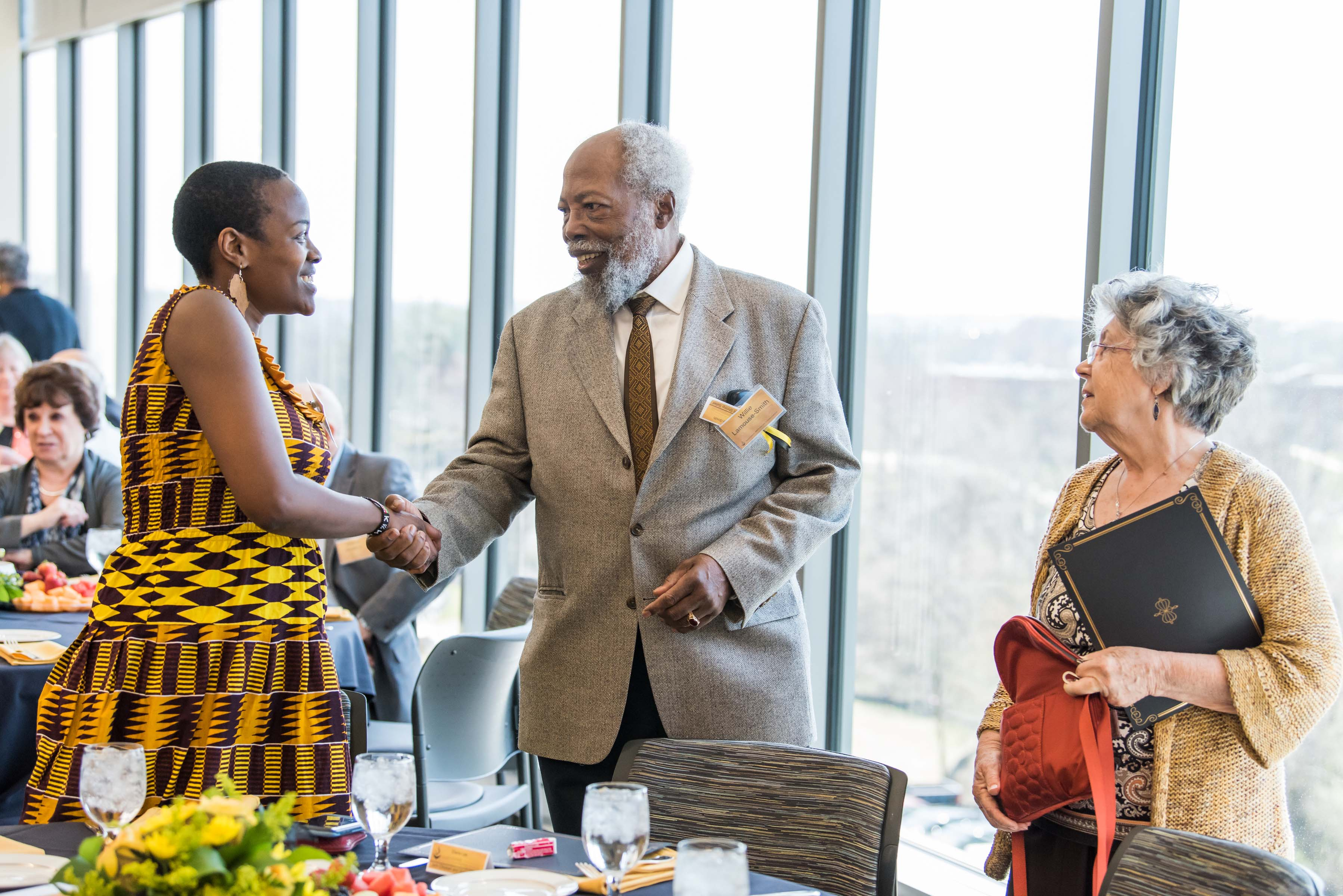 Naomi Mburu shakes mans hand as woman looks on at Wisdom Institute lunch