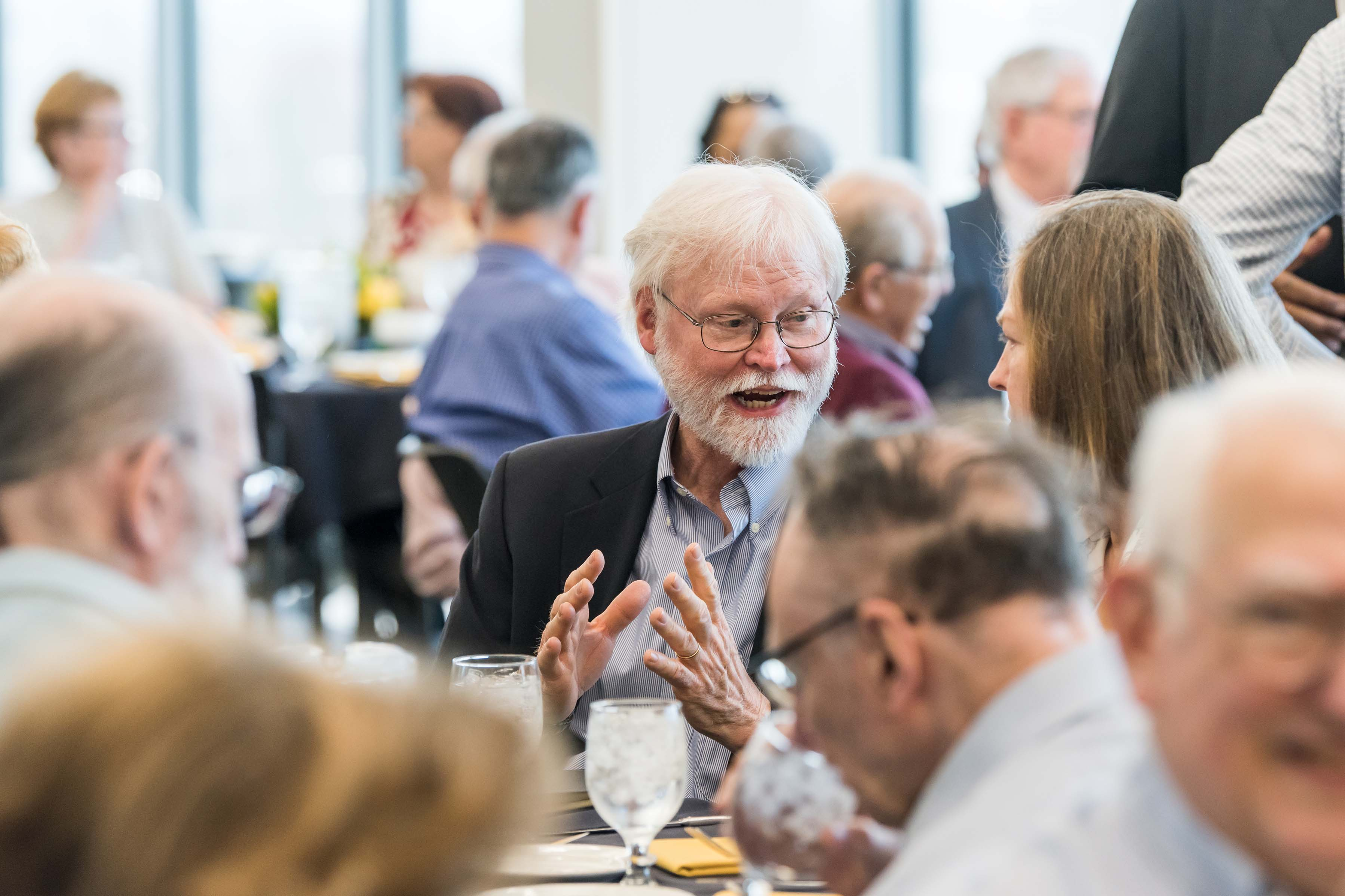 People in deep discussion around table at Wisdom Institute lunch