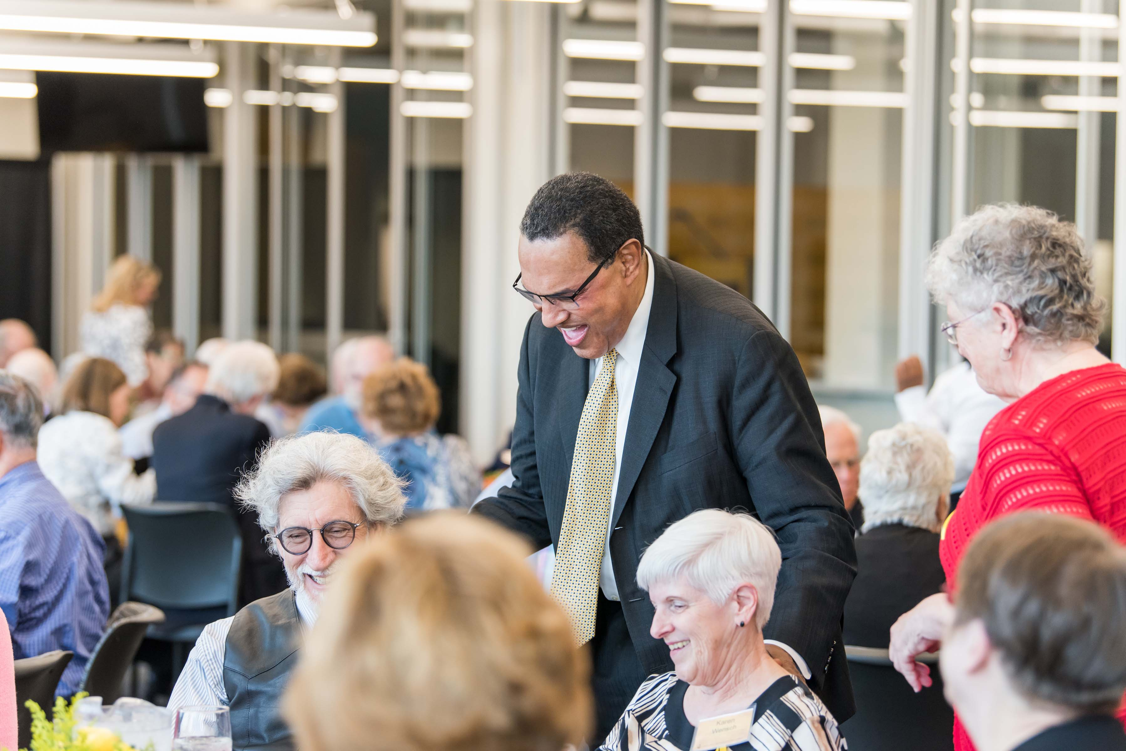 Hrabowski pats man sitting at table at Wisdom Institute lunch