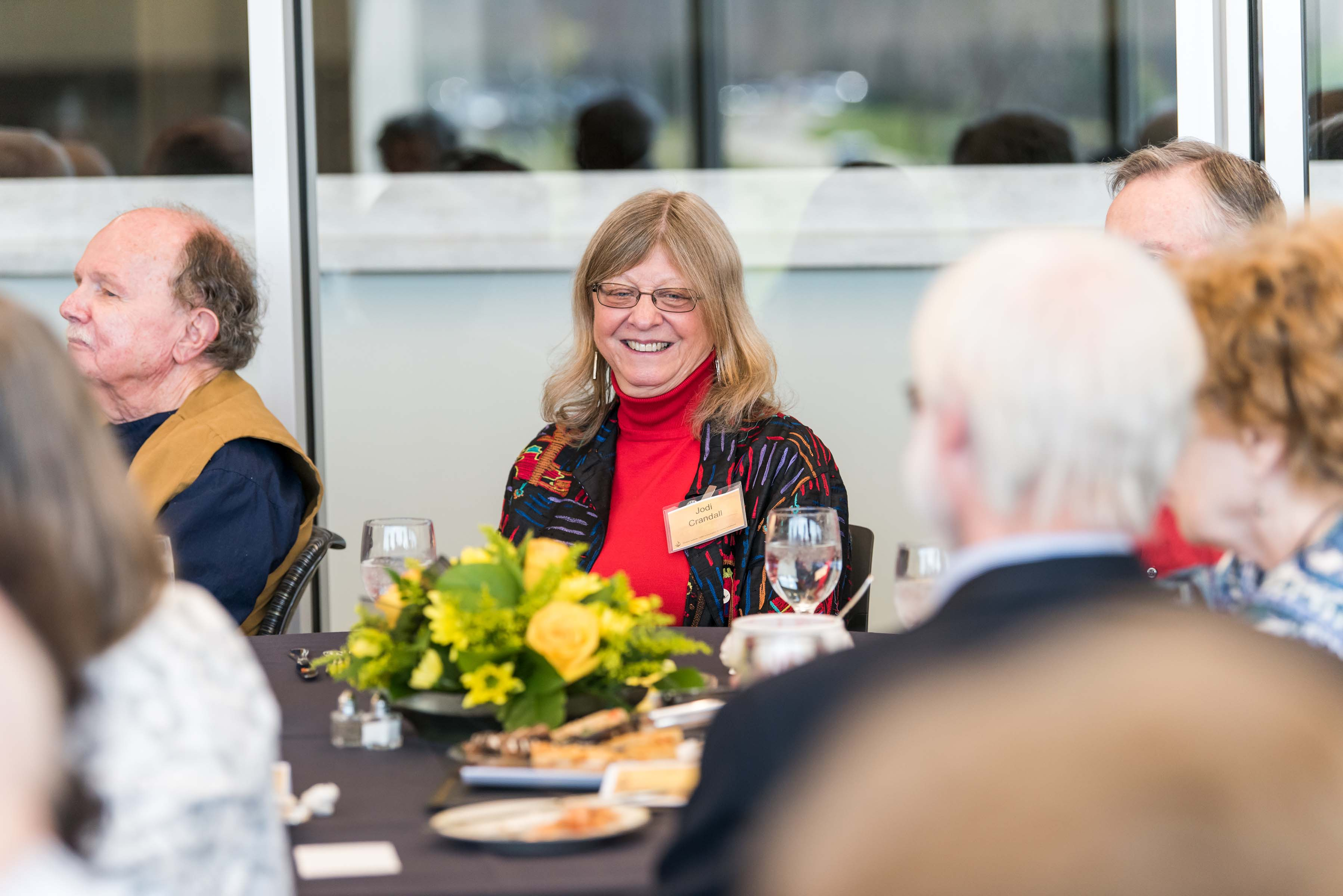 woman smile at table at Wisdom Institute lunch