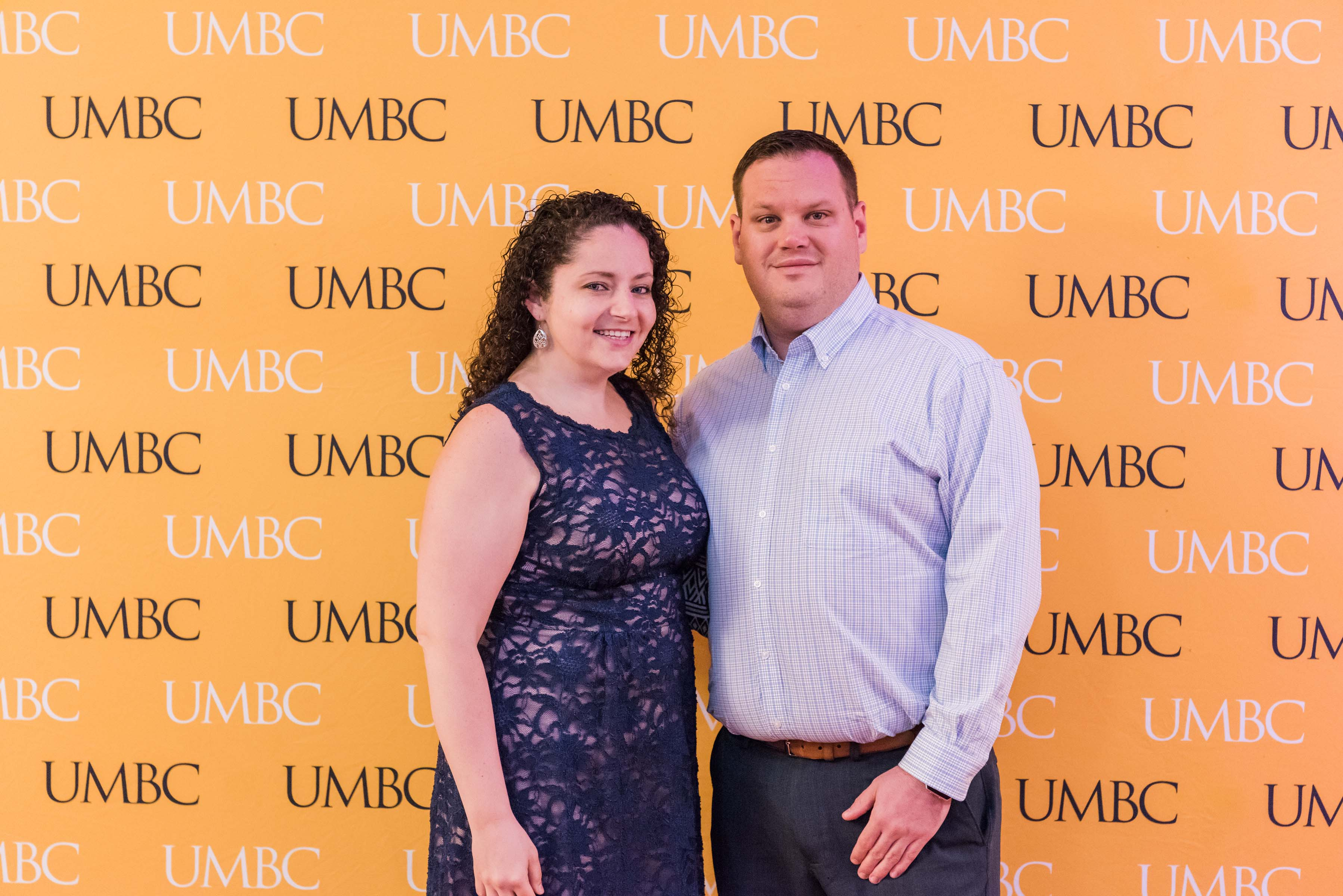 Man and woman pose together with UMBC wall for CYA wine tasting