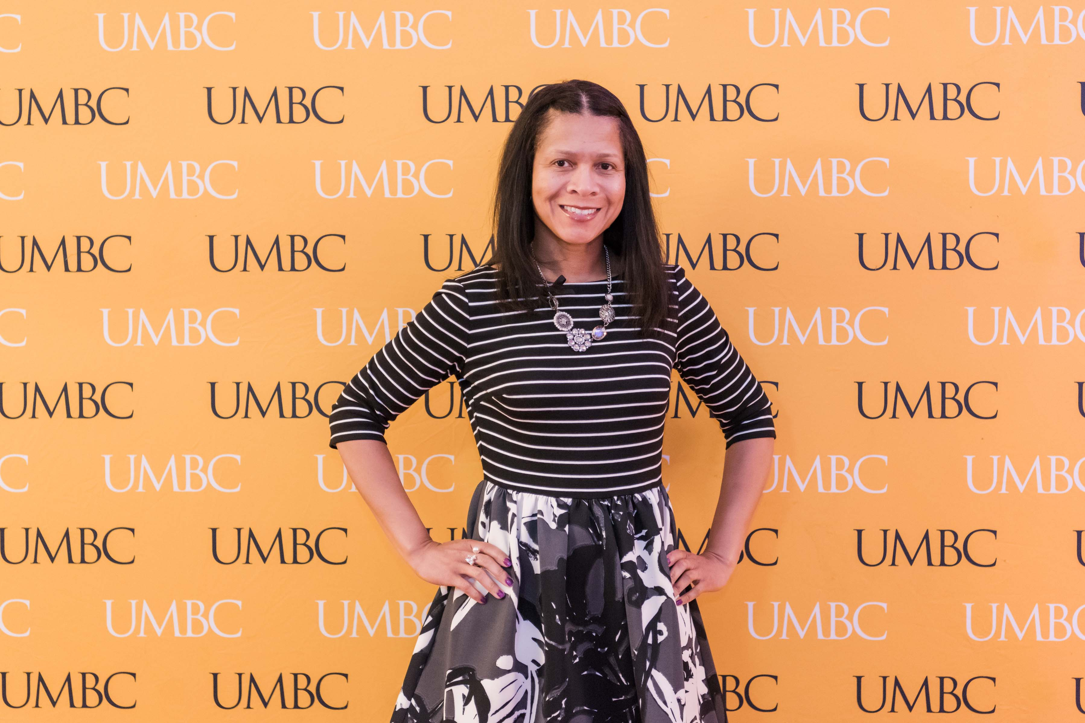 Woman poses with UMBC wall for wine tasting