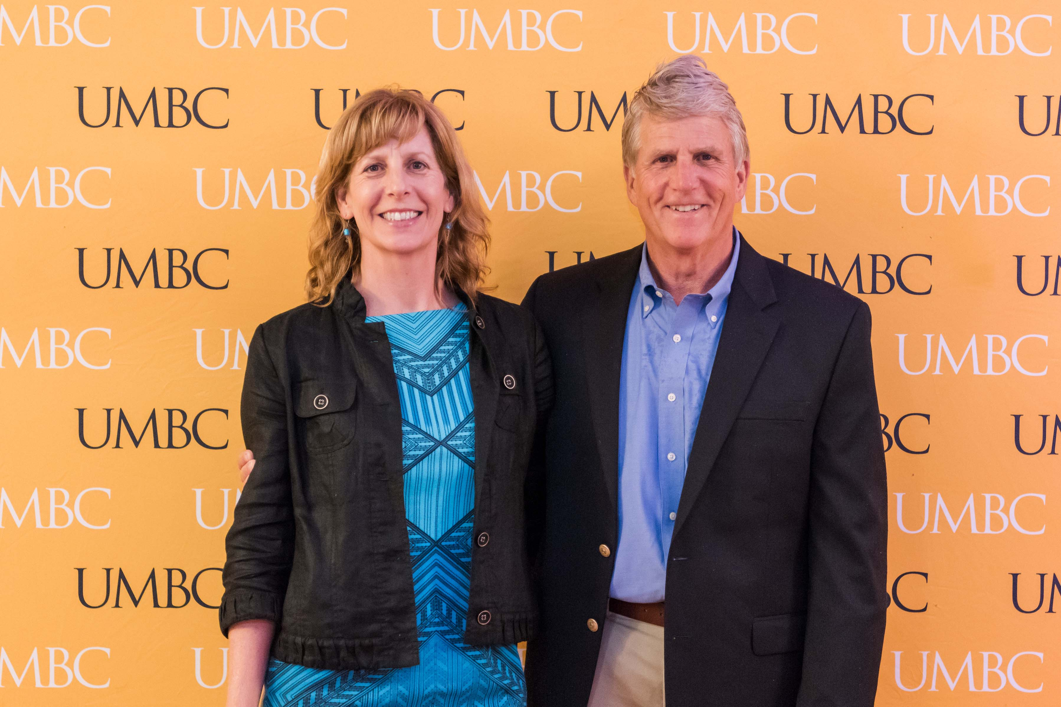Man and woman pose in front of UMBC wall for wine tasting