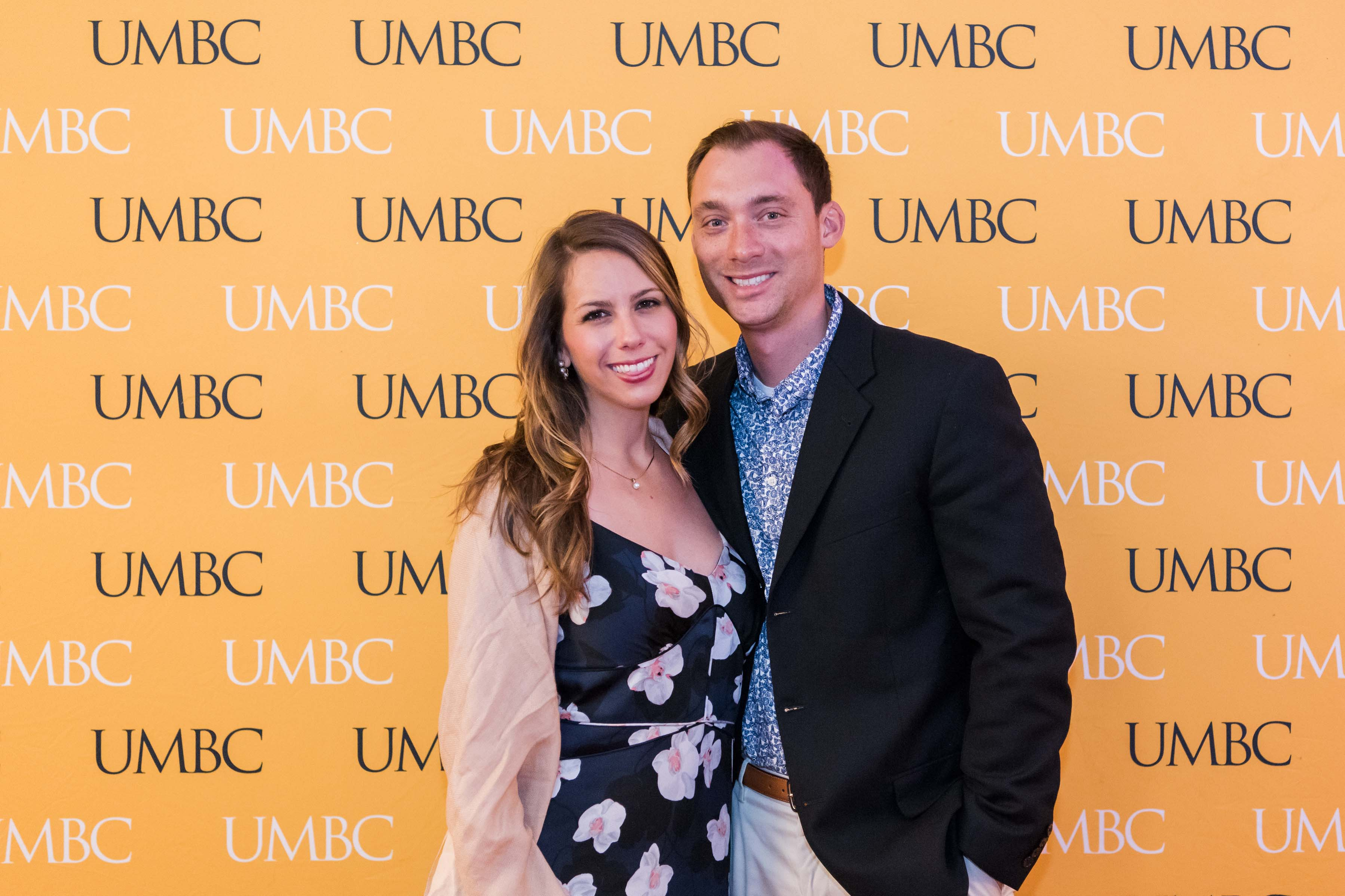 Couple pose together at wine tasting with UMBC wall
