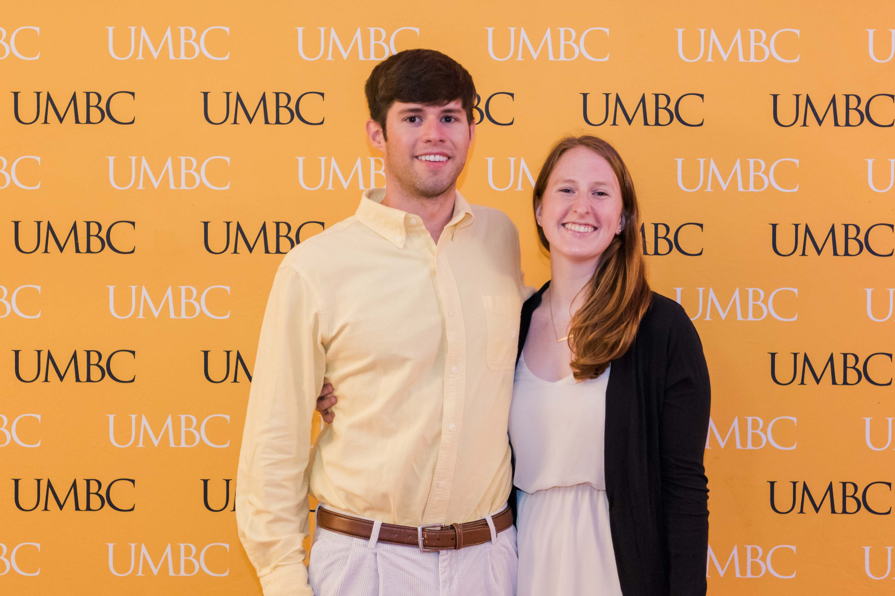Man and woman pose together in front of UMBC wall at CYA wine tasting
