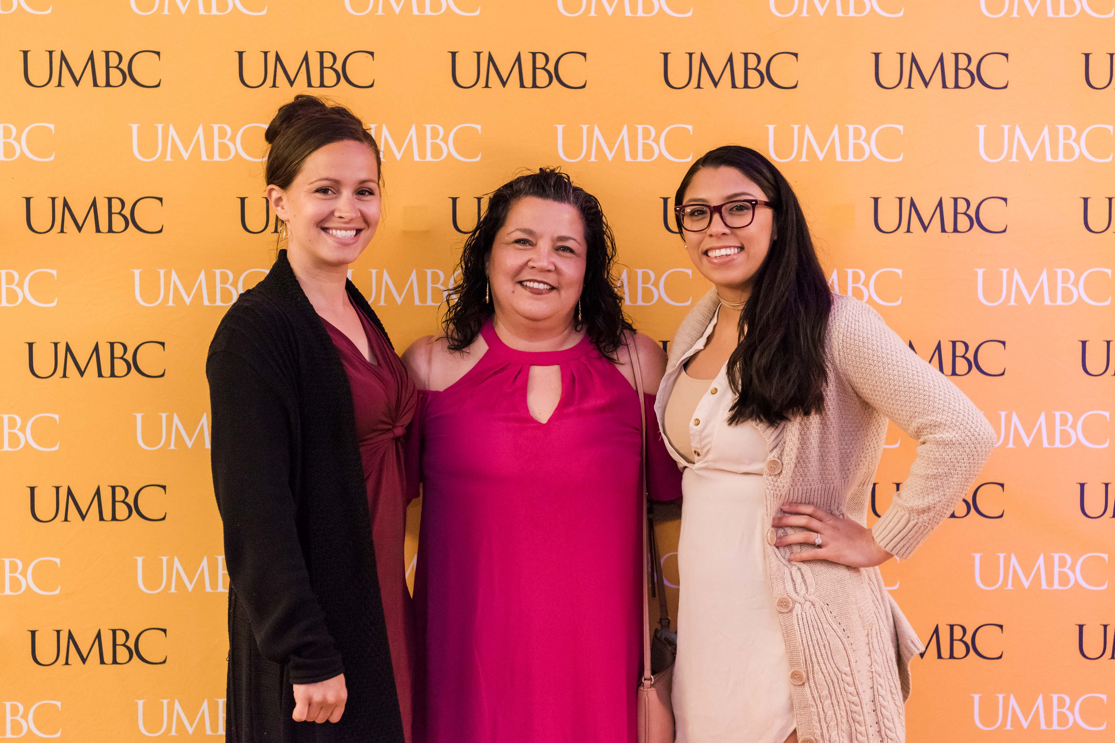 Three women pose together at UMBC wall for wine tasting event