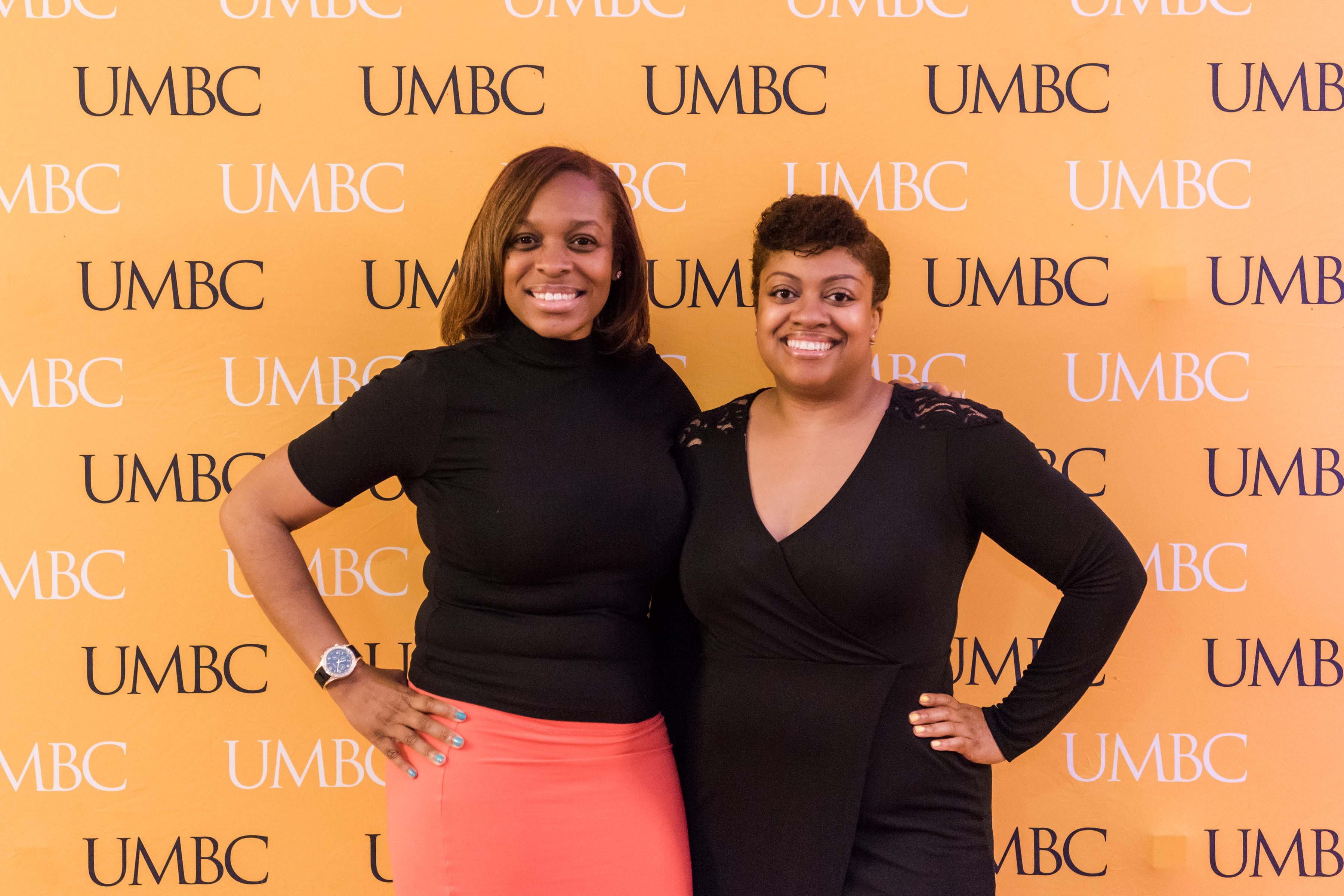 Two women pose with UMBC wall for CYA event