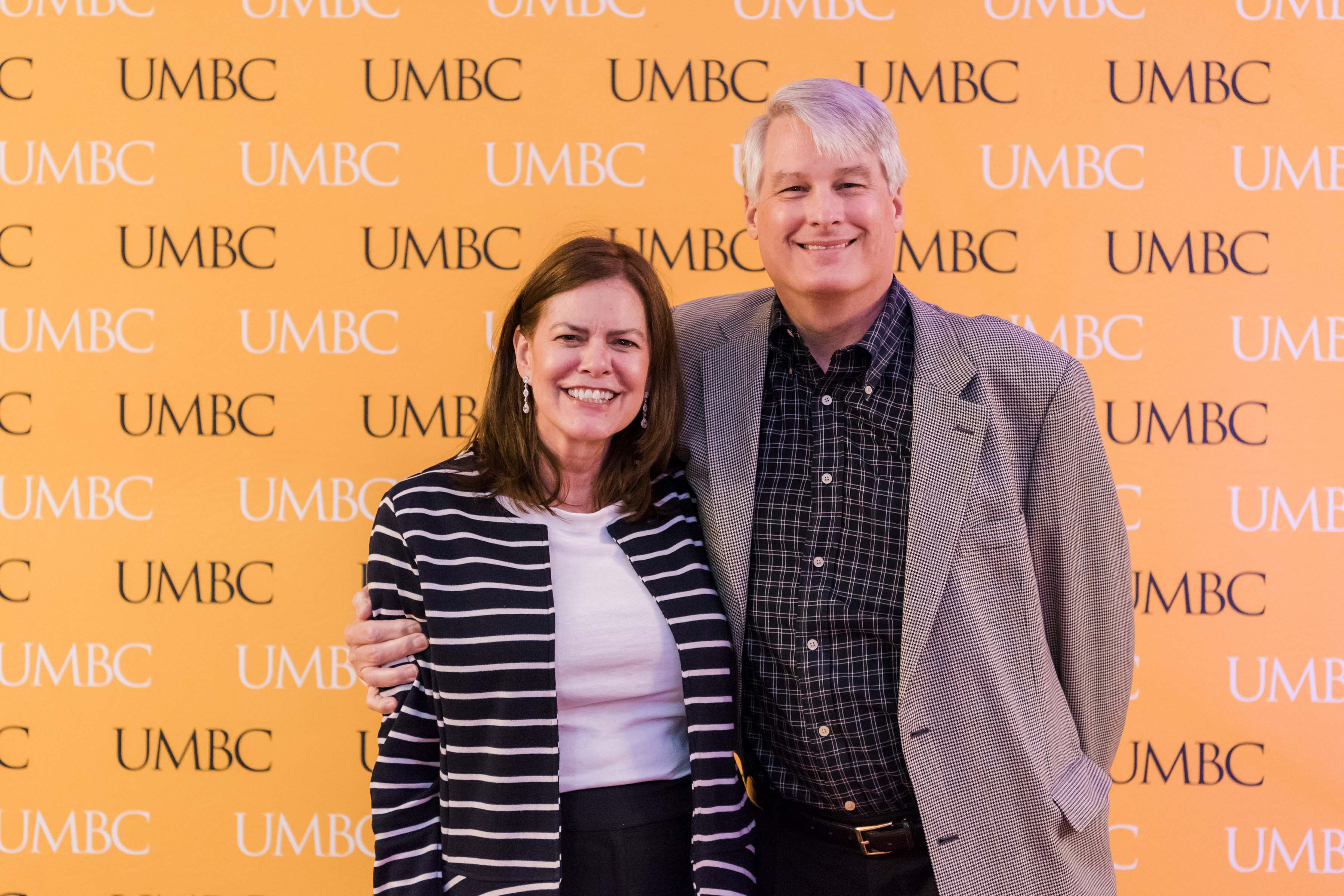 Man and woman pose in front of UMBC wall for CYA event